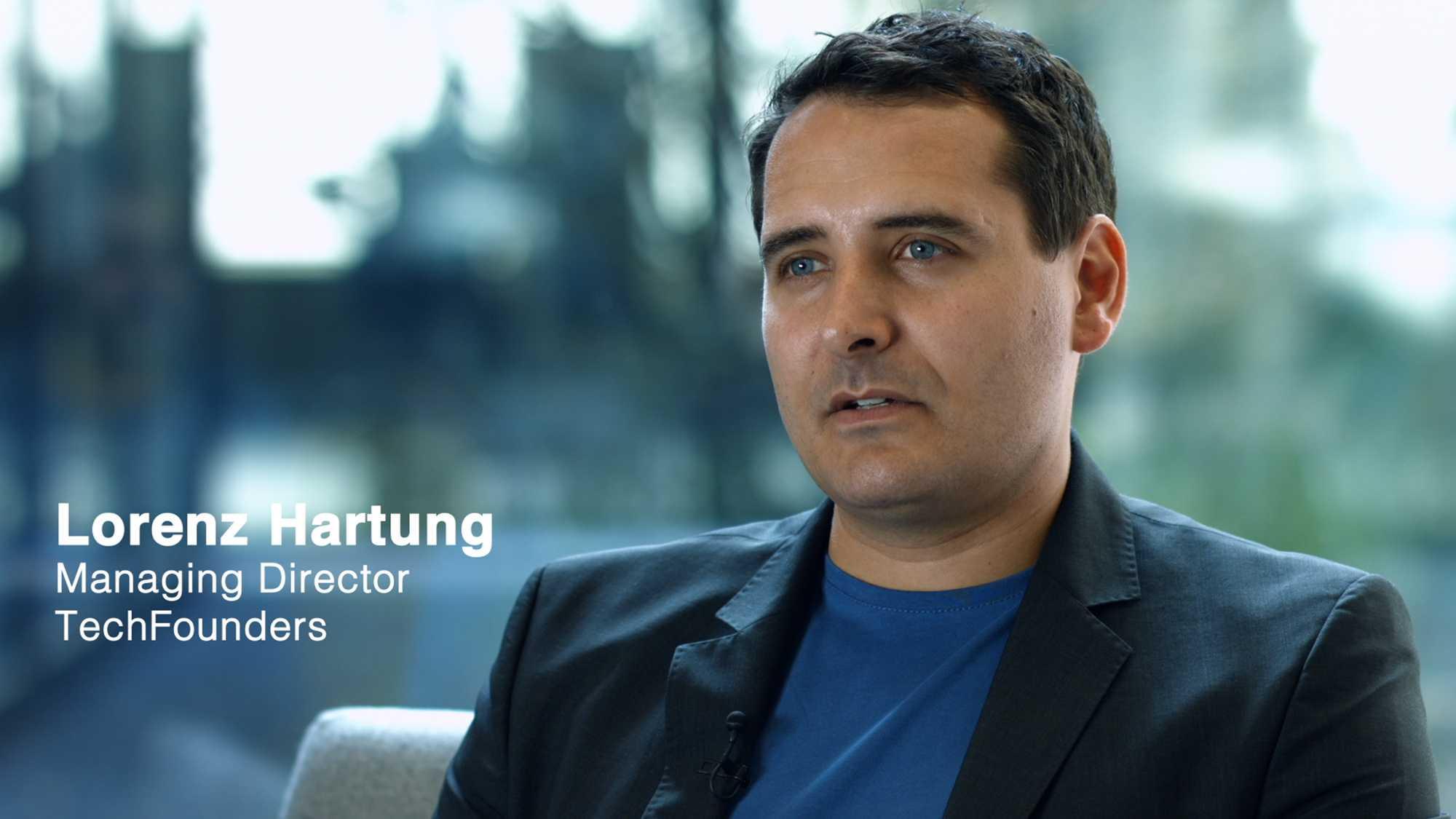 Das Bild zeigt einen Mann, der ein schwarzes Sakko trägt. Darunter trägt er ein blaues T-Shirt. Neben ihm ist sein Name und seine Position ins Bild getracked worden, er heißt Lorenz Hartung und ist Managing Director of TechFounders. Das Bild dient als Sliderbild für den Portfolioeintrag UnternehmerTUM – Techfounders von Panda Pictures.
