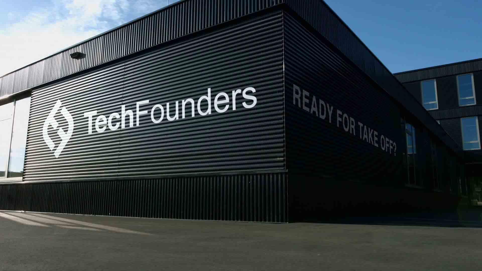 """Das Bild zeigt ein schwarzes Gebäude. dieses Gebäude steht vor einer Straße. Auf dem Gebäude ist ein weißer Schriftzug uzt lesen. Man liest das Wort """"TechFounders"""" daneben ist ihr Logo angebracht. Das Bild dient als Sliderbild für den Portfolioeintrag UnternehmerTUM – Techfounders von Panda Pictures."""