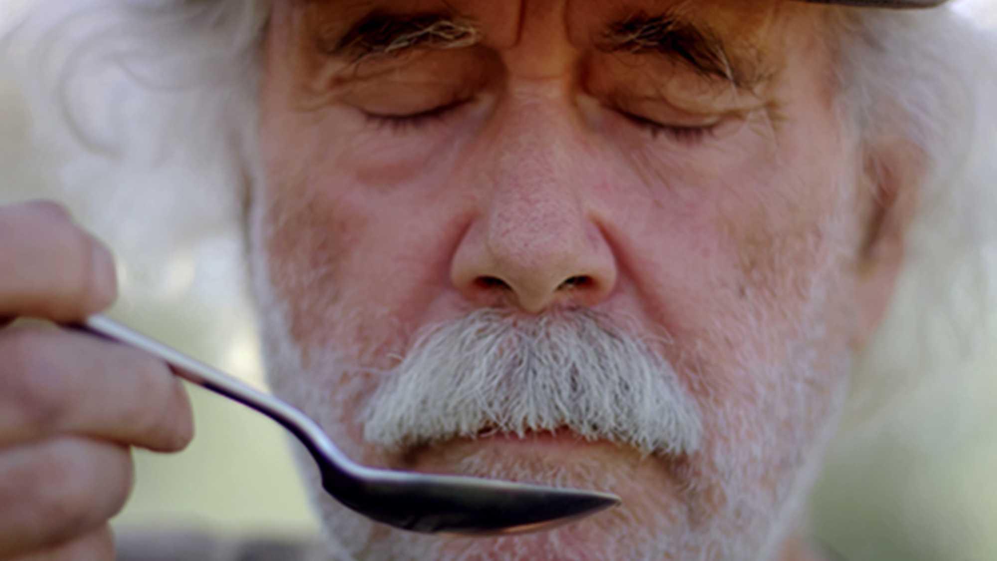Das Bild zeigt einen Mann. Sein Gesicht ist zu sehen. Vor sein Gesicht hält er einen Löffel in der Farbe silber. Seine Augen sind geschlossen. Er hat weißes Haar und trägt einen weißen Oberlippenbart. Das Bild dient als Sliderbild für den Portfolioeintrag Kurzfilm Tränen der Olive von Panda Pictures.