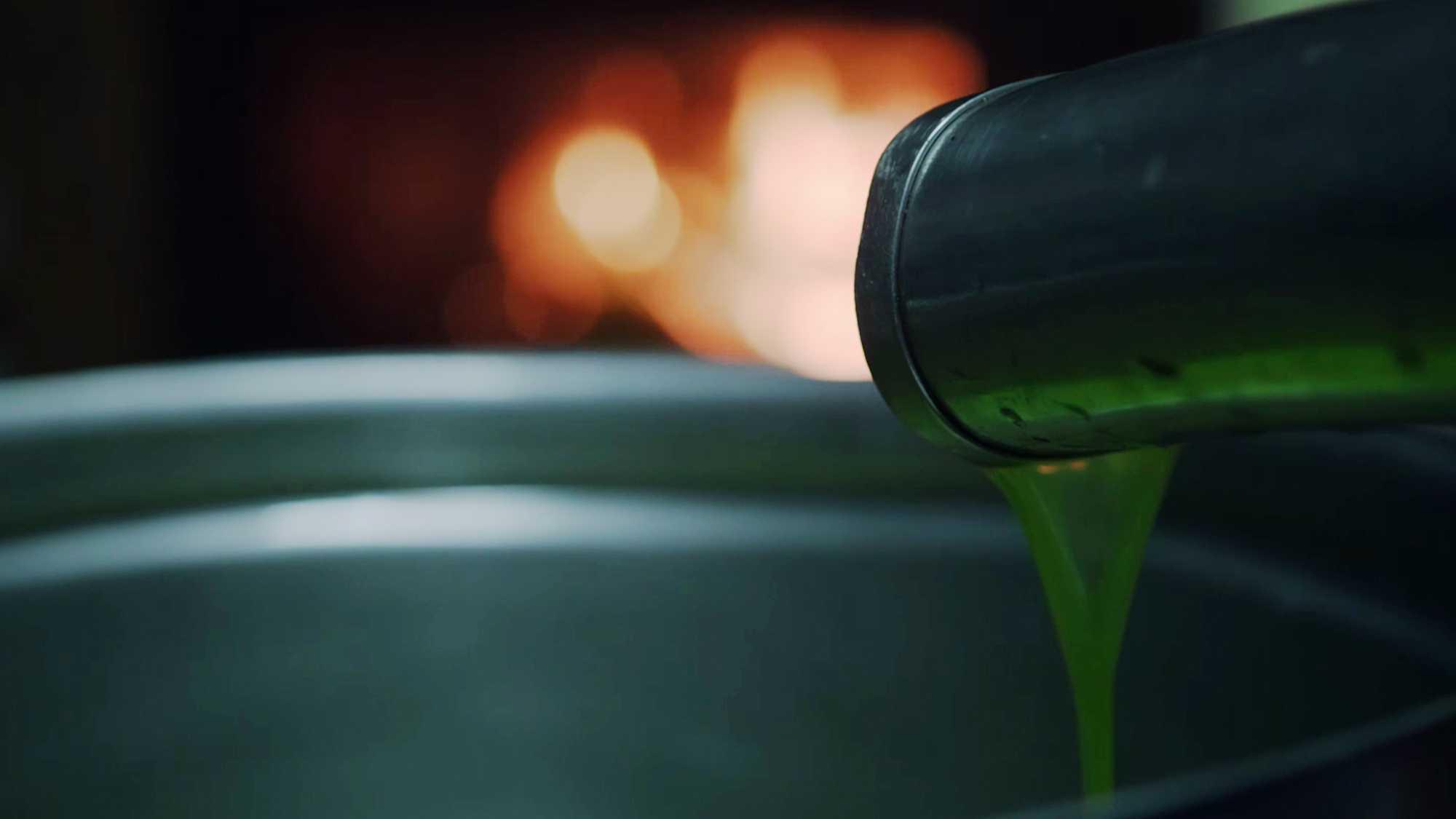 Das Bild zeigt eine silberne Röhre, die grünes Öl in einen Eimer fließen lässt. Dahinter ist ein verschwommenes Licht zu sehen. Das Bild dient als Sliderbild für den Portfolioeintrag Kurzfilm Tränen der Olive von Panda Pictures.