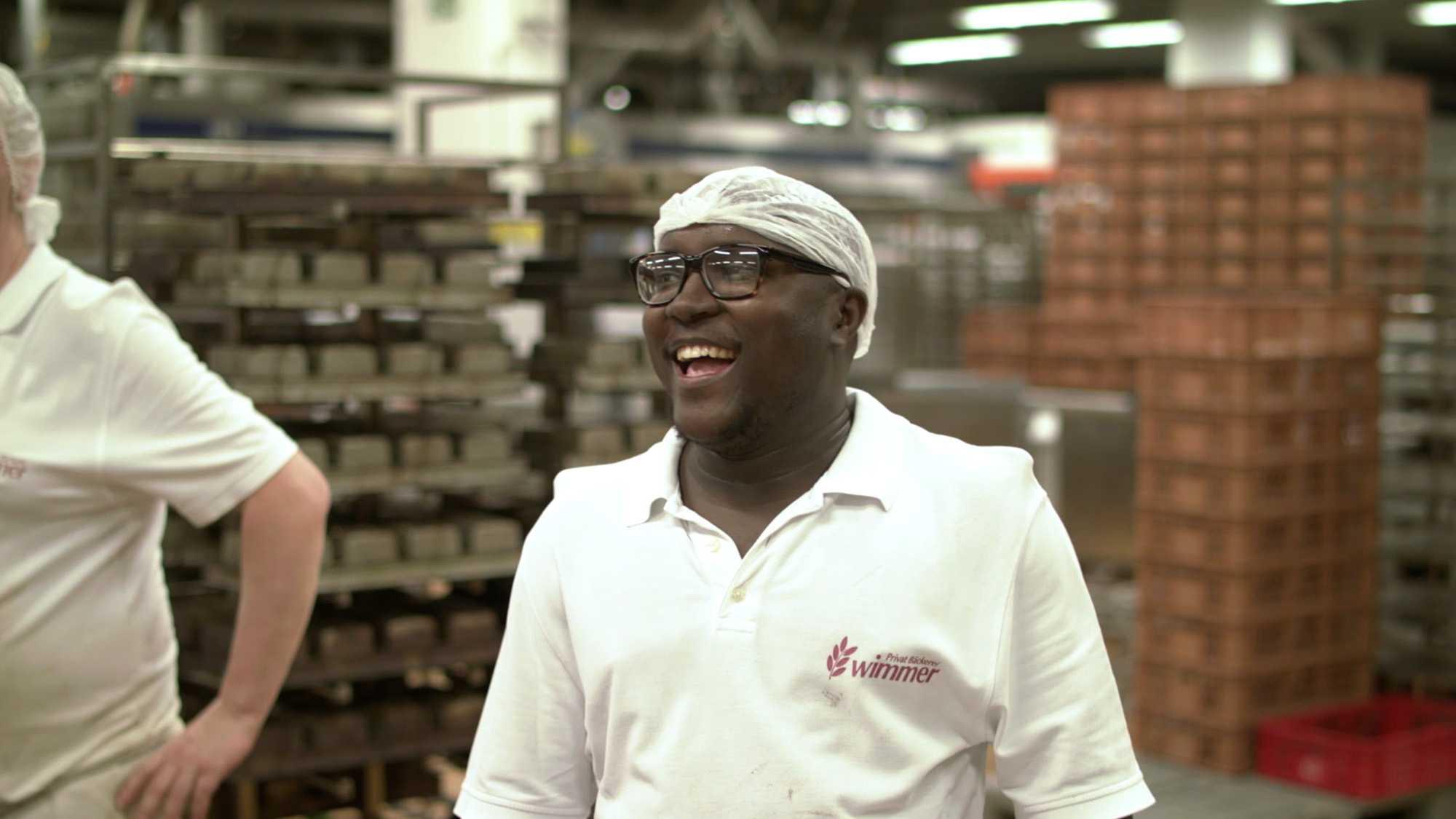 Das Bild zeigt einen lachenden Mann. Er trägt eine Haube auf seinem Kopf. Seine Kleidung ist weiß. Hinter ihm stehen Regale, in denen Brötchen gelagert werden. Das Bild dient als Sliderbild für den Portfolioeintrag Bäckerei Wimmer Produktfilm von Panda Pictures.
