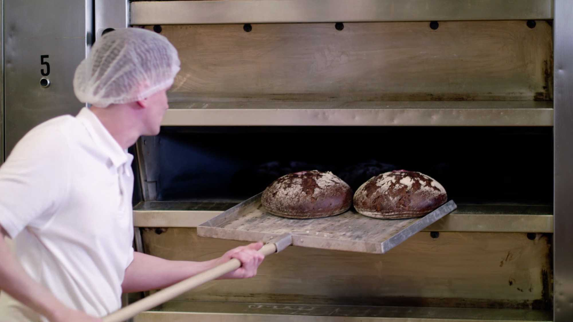 Das Bild zeigt einen Mann. Man sieht seinen Rücken. Er trägt auf seinem Kopf eine Haube. In seiner Hand hält er einen Spaten. Auf diesem Spaten liegen zwei Brote. Diese Brote holt er aus einem Ofen, der vor ihm steht. Das Bild dient als Sliderbild für den Portfolioeintrag Bäckerei Wimmer Produktfilm von Panda Pictures.
