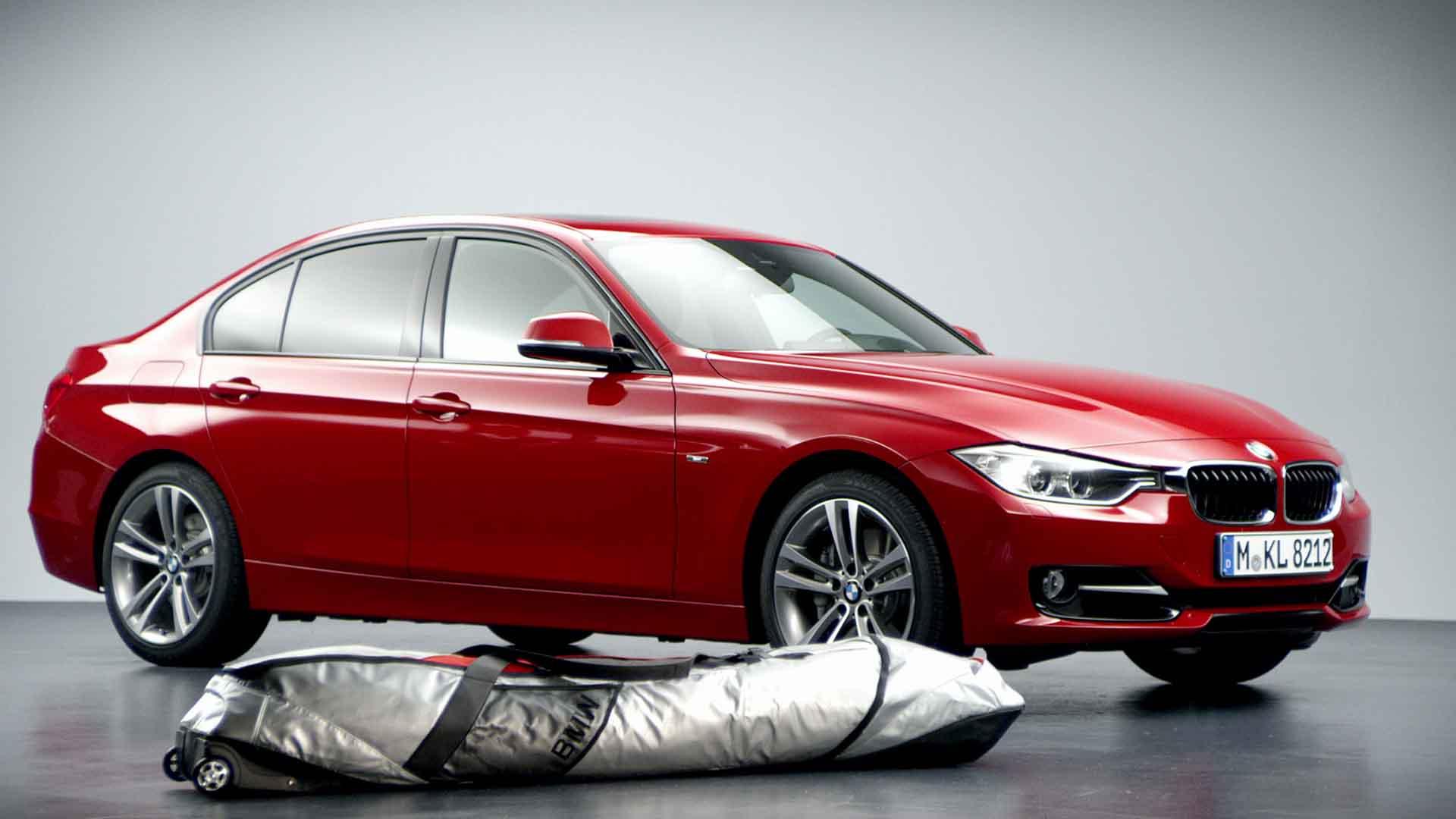 Das Bild zeigt ein rotes Auto. Es ist ein roter BMW. Man sieht ihn von der Seite. Vor ihm liegt eine Tasche, diese ist grau-weiß und zeigt ebenfalls das BMW Logo. Das Bild dient als Sliderbild für den Portfolioeintrag BMW F30 Zubehör von Panda Pictures.