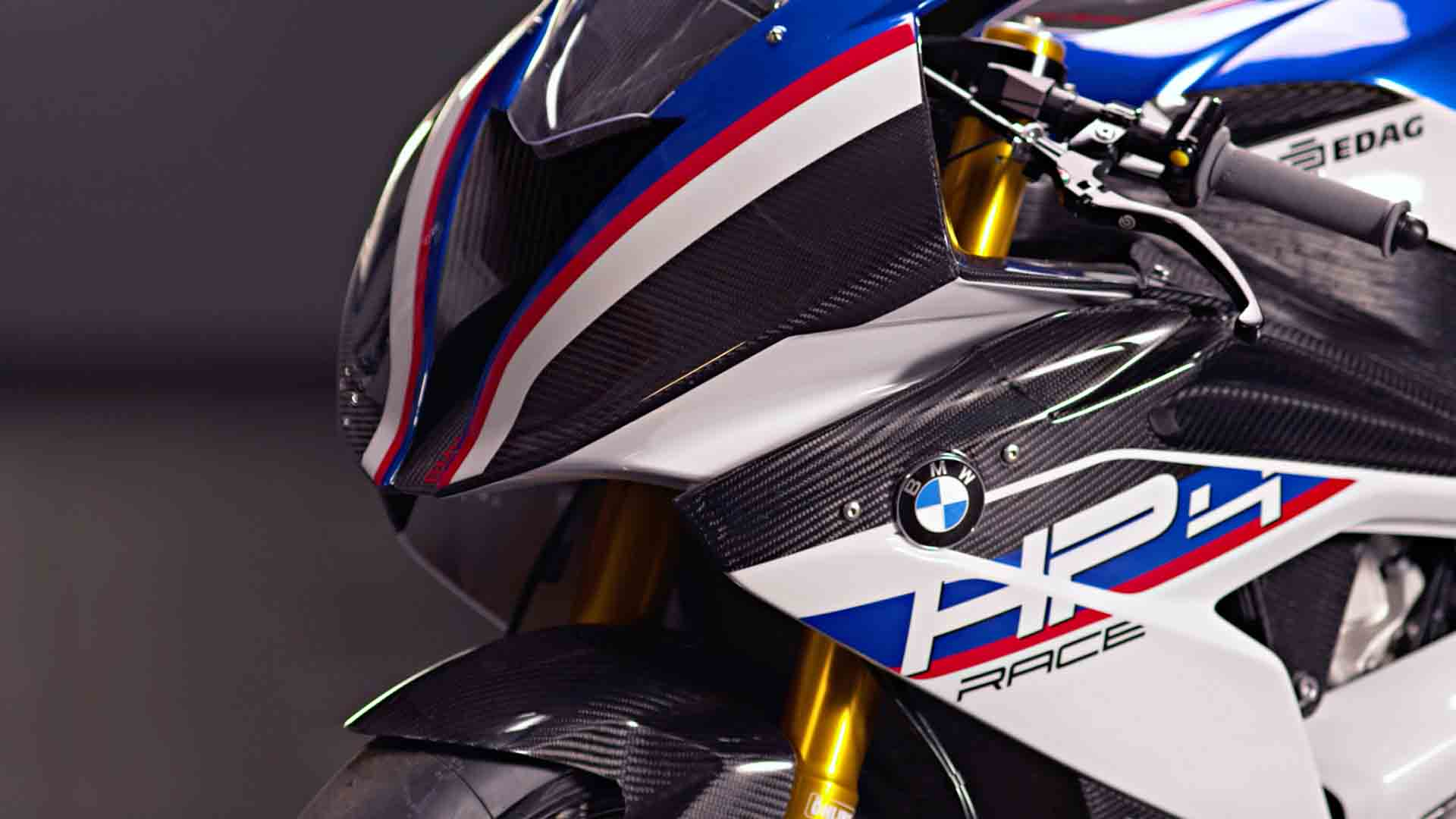 Das Bild zeigt ein Motorrad, das schwarz-blau-weiß-rot gestreift ist. Man sieht ein Logo von BMW. Das Bild zeigt nur die vordere Seite des Motorrads. Das Bild dient als Sliderbild für den Portfolioeintrag BMW Motorrad HP4 Race In the Spotlight von Panda Pictures.