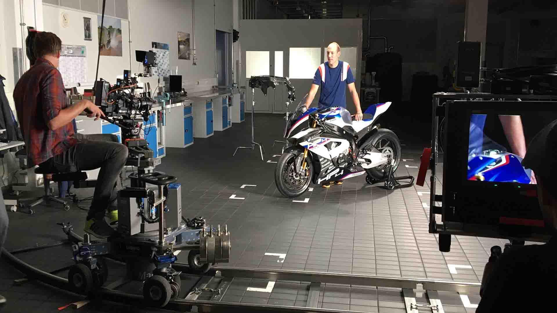 Das Bild zeigt einen Mann, der mit einem Motorrad in der Mitte einer Werkstatt steht. Vor ihm steht ein Mann mit einer Kamera. Er sitzt auf einem Stuhl und filmt den Mann mit dem Motorrad. Auf der rechten Seite des Bildes ist ein Monitor zu sehen. Dieser gibt das eingefangen Bild der Kamera wieder. Das Bild dient als Sliderbild für den Portfolioeintrag BMW Motorrad HP4 Race In the Spotlight von Panda Pictures.
