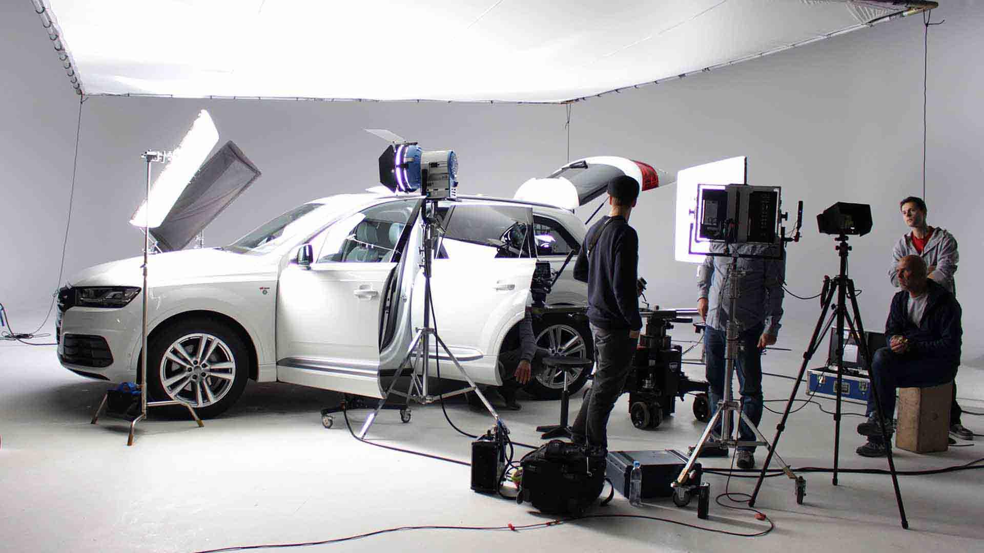 Das Bild zeigt ein weißes Auto. Es steht in einem Raum, welcher als Filmset verwendet wird. Das Auto wird von Kameras gefilmt und von Lichtern beleuchtet. Dieses ganze Equipment steht rechts. Dabei stehen noch einige Menschen. Das Bild dient als Sliderbild für den Portfolioeintrag RECARO Child Safety – Einbaufilme von Panda Pictures.
