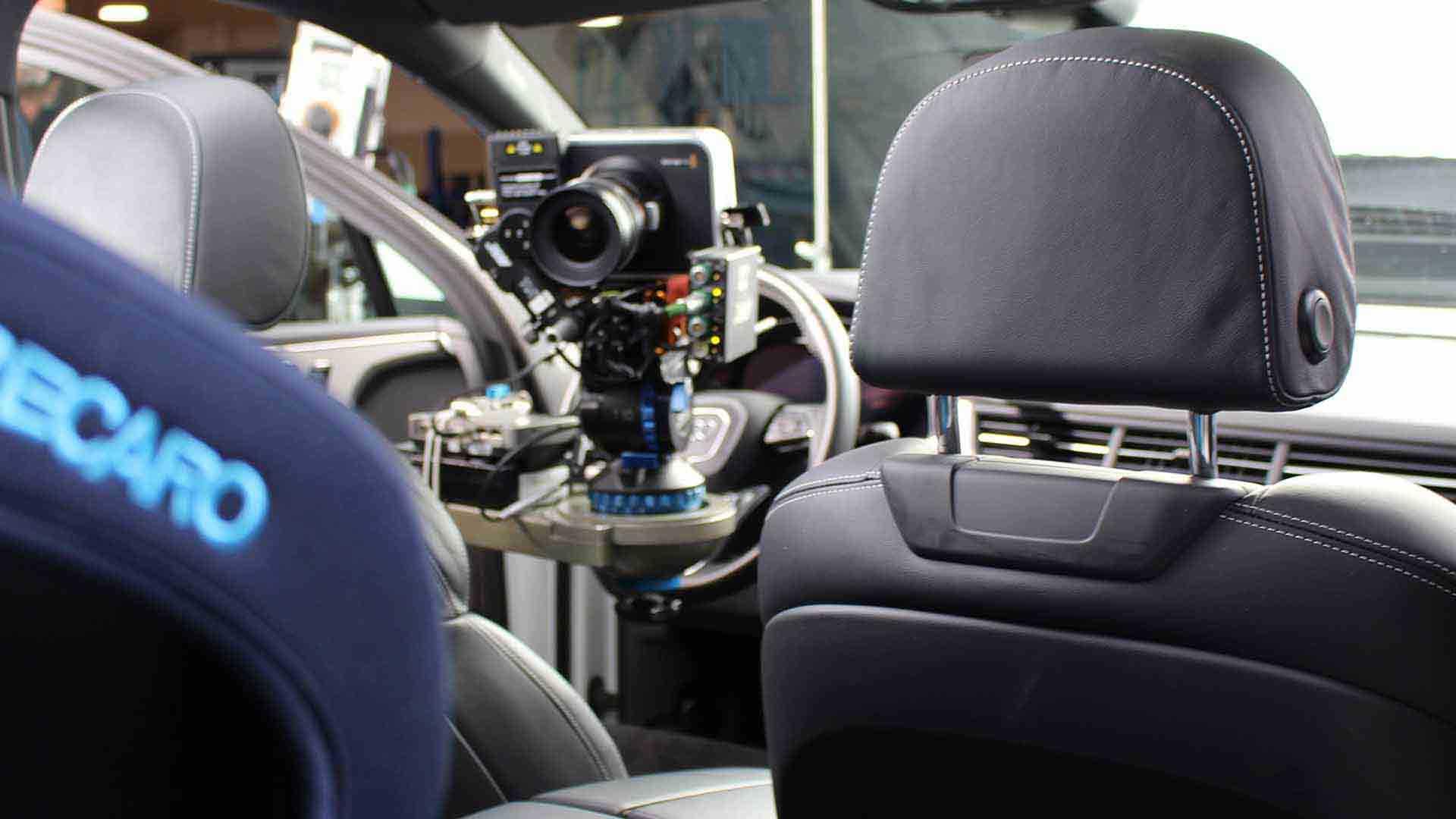Das Bild zeigt eine Kamera, die an einem Lenkrad in einem Auto befestigt wurde. Diese filmt einen Kindersitz, der auf der Rückbank zu sehen ist. Das Logo Recaro verrät seine Herkunft. Das Bild dient als Sliderbild für den Portfolioeintrag RECARO Child Safety – Einbaufilme von Panda Pictures.