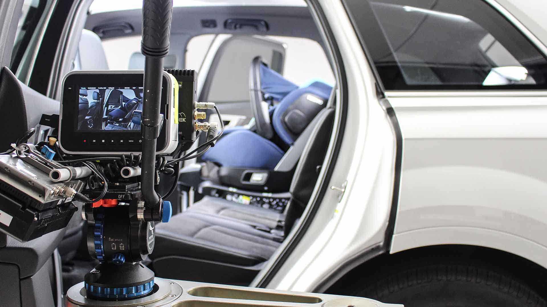 Das Bild zeigt einen Ausschnitt eines Autos. Man sieht den hinteren Teil. Das Auto ist weiß. Auf diesen ist eine Kamera gerichtet. Sie filmt durch eine offene Türe einen Kindersitz. Dieser ist blau. Man sieht ihn auch auf dem Kameramonitor der an der Kamera angebracht ist. Das Bild dient als Sliderbild für den Portfolioeintrag RECARO Child Safety – Einbaufilme von Panda Pictures.