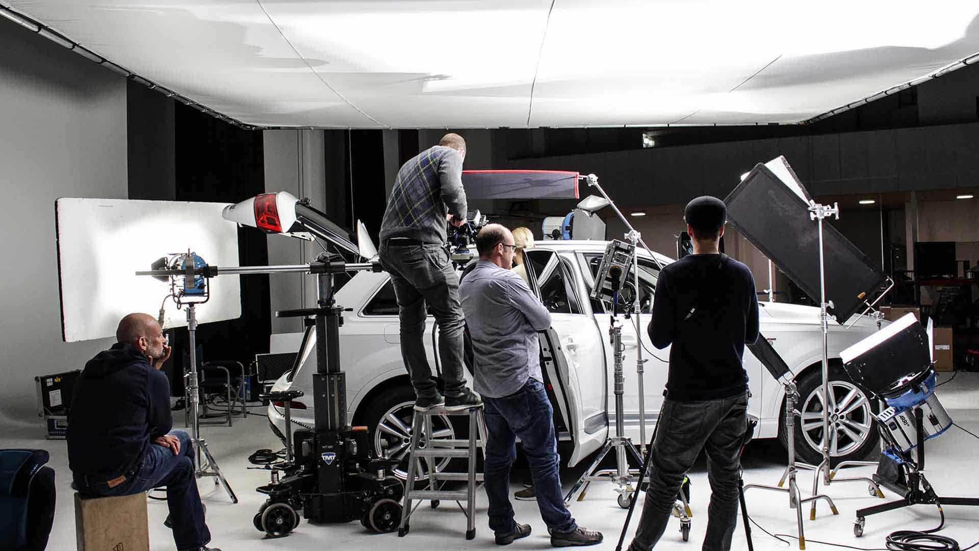 Das Bild zeigt ein weißes Auto. Es steht in einem Raum auf einer Leinwand. Um das Auto herum stehen viele Männer. Sie filmen das Auto. Über dem Auto hängt ein Licht. Das Bild dient als Sliderbild für den Portfolioeintrag RECARO Child Safety – Einbaufilme von Panda Pictures.