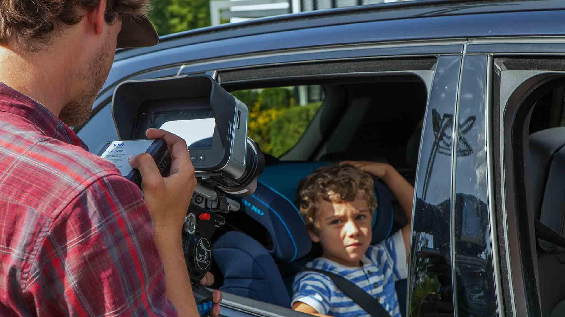 Das Bild zeigt das Rückbankfenster eines Fahrzeugs. Es ist geöffnet. In einem Kindersitz sitzt ein Kind. Auf dieses Kind ist eine Kamera gerichtet. Diese wird von einem Mann gehalten, der vor dem Auto steht. Das Bild dient als Sliderbild für den Portfolioeintrag RECARO Child Safety – Childseats Save Lives von Panda Pictures.
