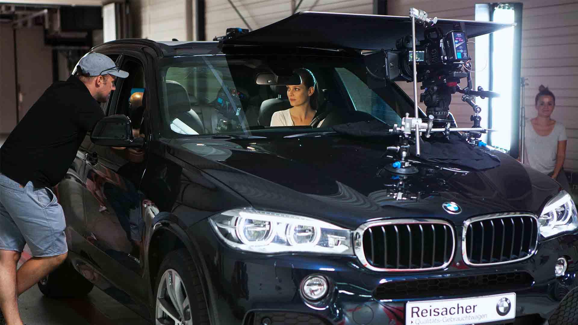 Das Bild zeigt einen schwarzen BMW. Er steht in einem Raum. Auf der Motorhaube des Autos ist eine Kamera angebracht, sie ist auf den Fahrersitz des Wagens gerichtet. Auf diesem sitzt eine Frau. Durch das Fenster an der Beifahrerseite lehnt sich ein Mann. Er spricht mit ihr. Das Bild dient als Sliderbild für den Portfolioeintrag RECARO Child Safety – Childseats Save Lives von Panda Pictures.