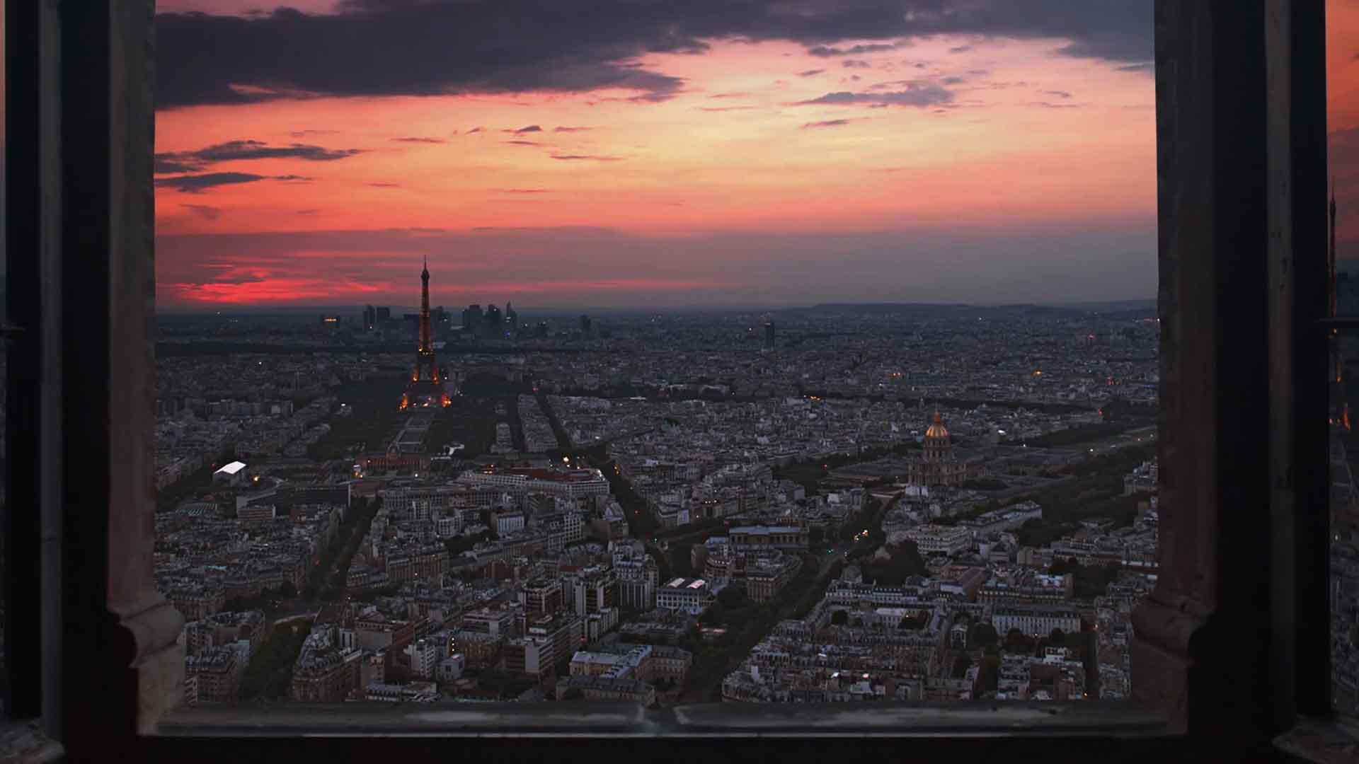Das Bild zeigt die Aussicht auf eine Stadt. Die Sonne geht unter, die Stadt liegt in der Abenddämmerung. Das Bild wurde aus einem Hotelzimmer aufgenommen, die rechte und linke Seite zeigt die Vorhänge. Das Bild dient als Sliderbild für den Portfolioeintrag Engel und Völkers Recruitingfilm von Panda Pictures.