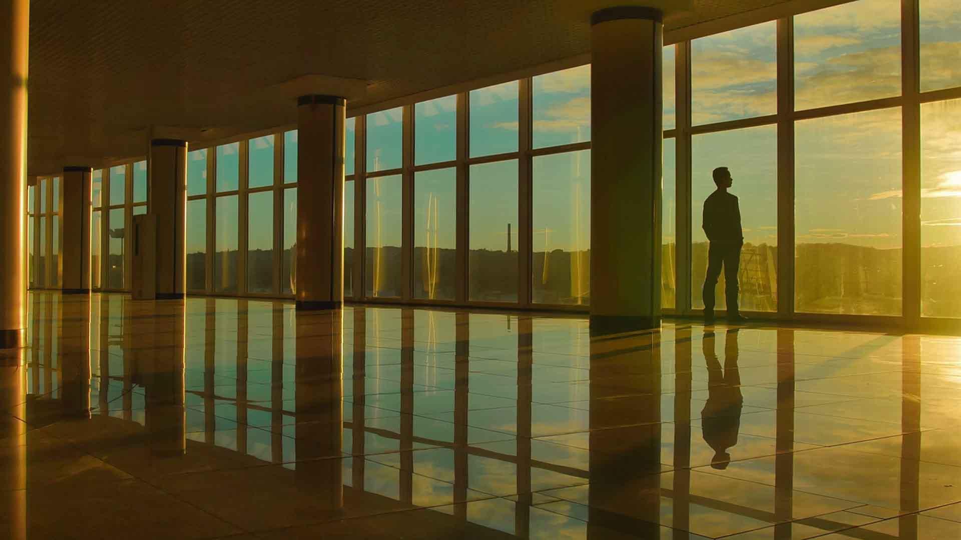 Das Bild zeigt einen Saal, in welchem sich auf dem Boden die Fenster an den Wänden Wiederspiegeln. Auf der rechten, vorderen Seite steht ein Mann, er beobachtet das Sonnenlicht durch das Fenster. Das Bild dient als Sliderbild für den Portfolioeintrag Engel und Völkers Recruitingfilm von Panda Pictures.