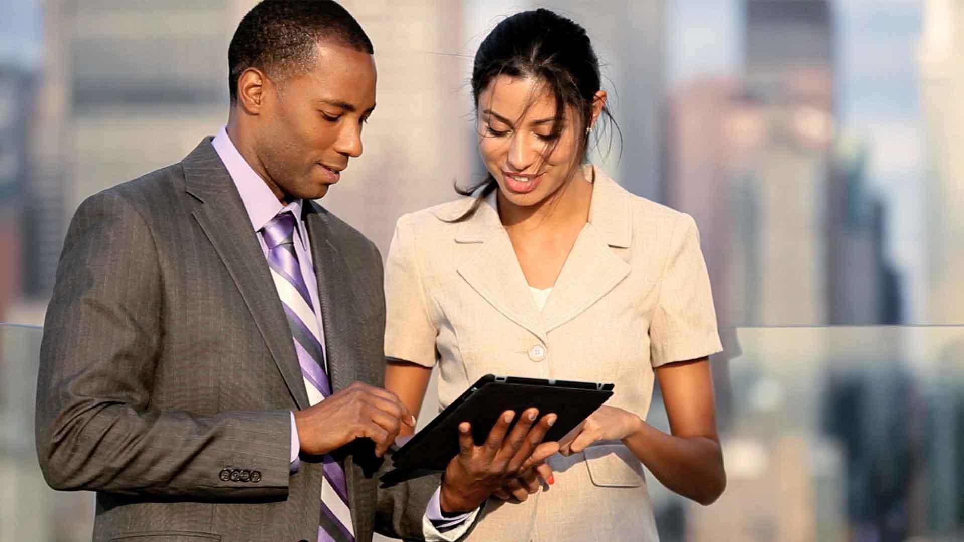 Das Bild zeigt ein Paar. Ein Mann und eine Frau stehen nebeneinander und schauen in ein Tablet, das sie in der Hand halten. Hinter den beiden sieht man als Silhouette Hochhäuser. Das Bild dient als Sliderbild für den Portfolioeintrag Engel und Völkers Recruitingfilm von Panda Pictures.