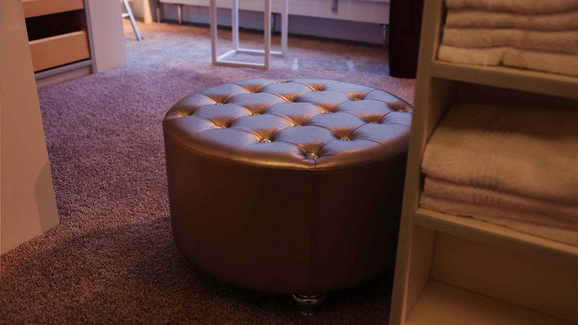 Das Bild zeigt einen Hocker der auf einem lila Teppich steht. Er ist braun gefärbt. Neben dem Hocker steht ein Regal. Dieses Regal ist aus Holz. Im Hintergrund sieht Tischbeine. Das Bild dient als Sliderbild für den Portfolioeintrag Zamaro von Panda Pictures.