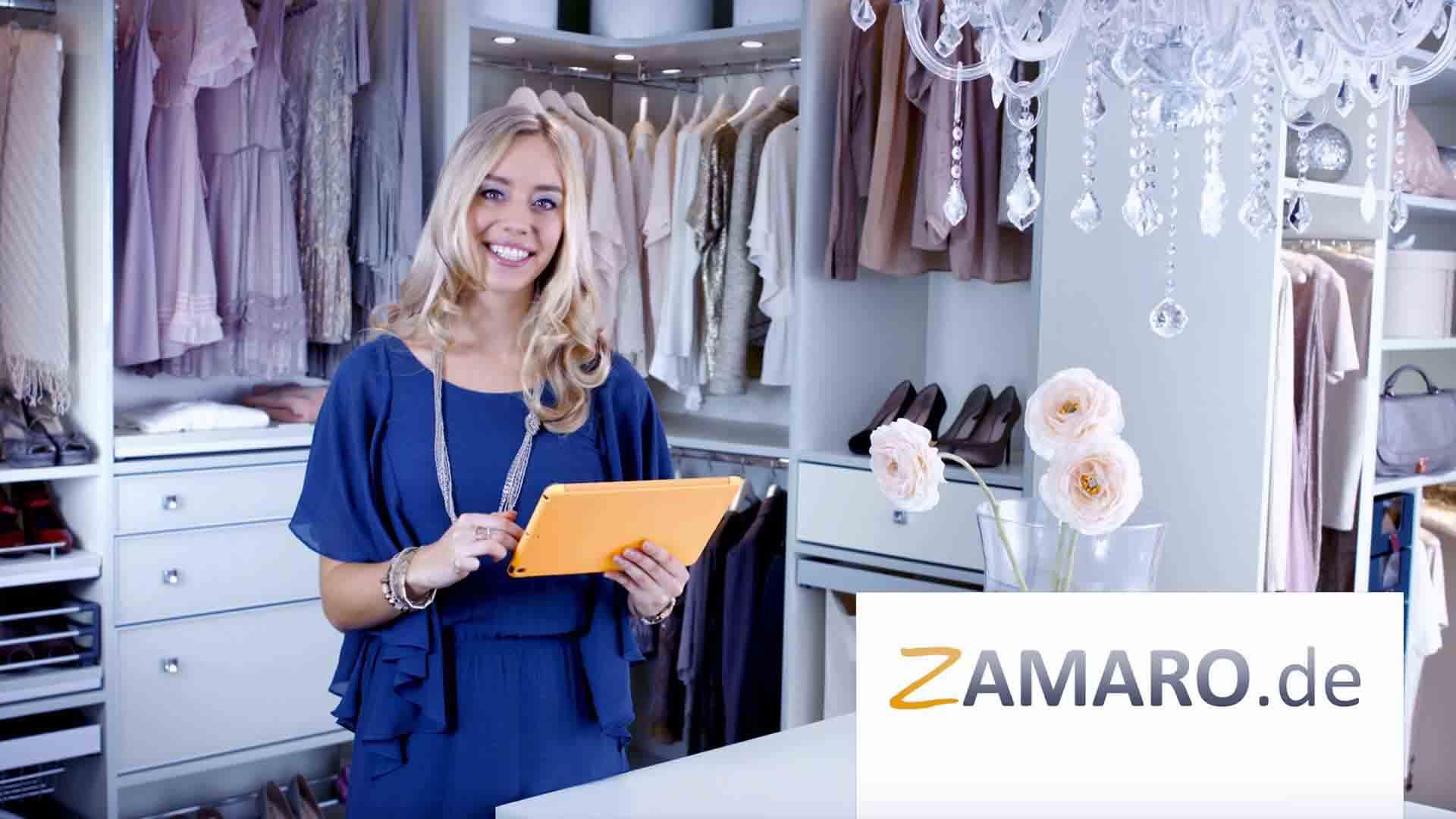 Das Bild zeigt eine Frau, die in einem Kleiderschranks steht. Sie trägt ein blaues Kleid mit Kette. Sie ist blond und lacht. In ihrer Hand hält sie ein gelbes Tablet. Das Bild dient als Sliderbild für den Portfolioeintrag Zamaro von Panda Pictures.