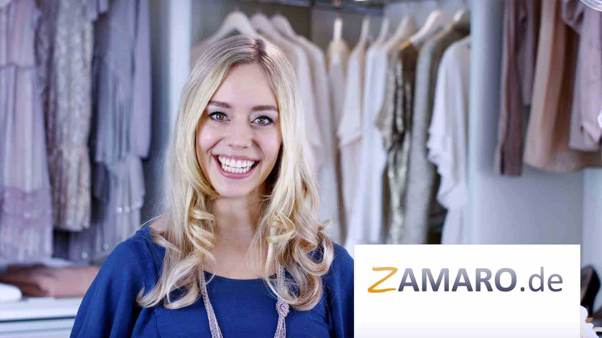 """Das Bild zeigt eine Frau. Sie hat blonde Haare. Sie trägt ein blaues Kleid. Dazu trägt sie eine Kette. Im Hintergrund sieht man Kleider hängen, sie befindet sich in einem begehbaren Kleiderschrank. Auf der rechten Seite des Bildes sieht man einen weißen Banner auf dem """"Zamaro.de"""" steht. Das Bild dient als Sliderbild für den Portfolioeintrag Zamaro von Panda Pictures."""