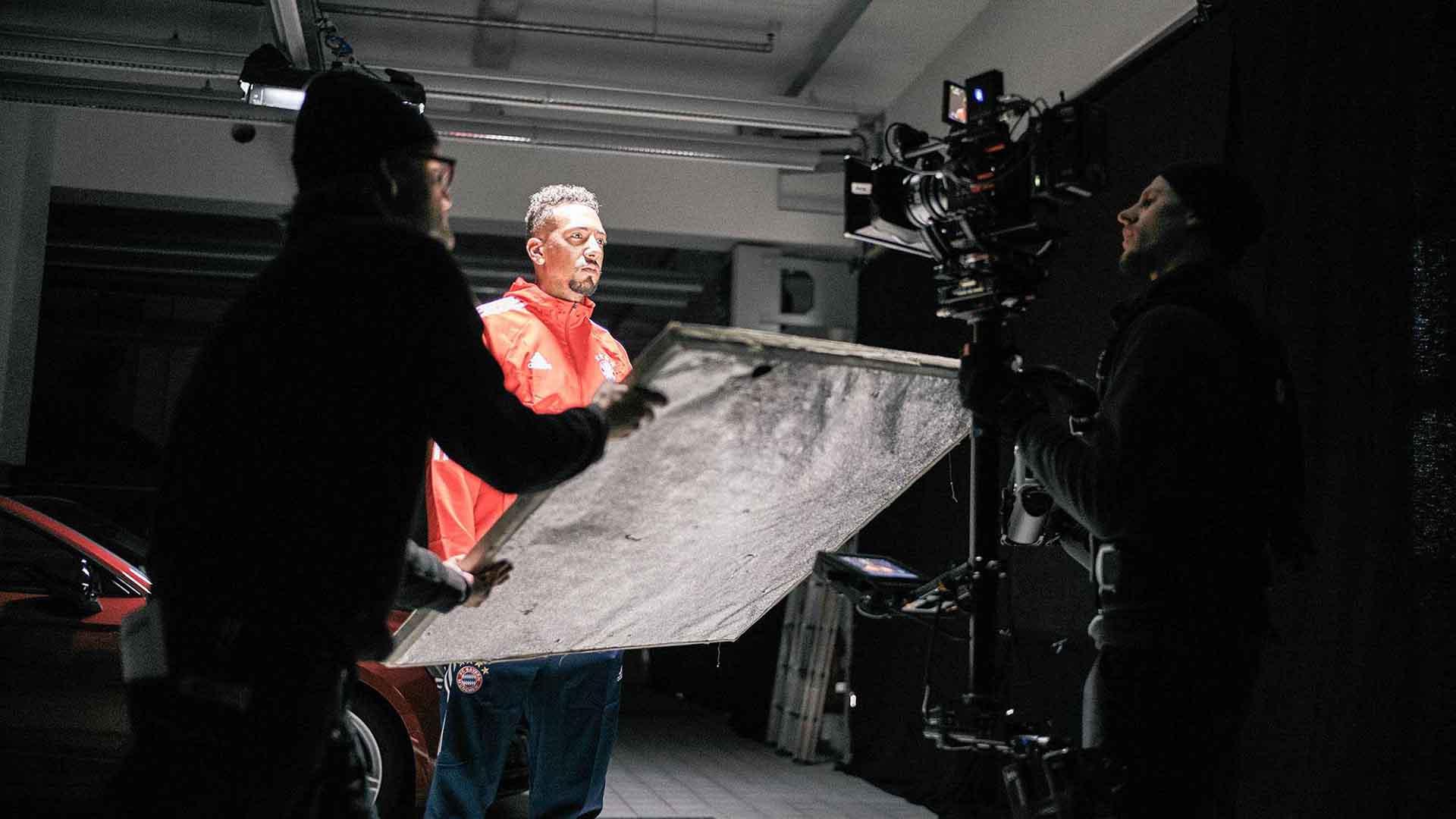 Das Bild zeigt einen Fussballer des FC Bayern München. Es ist Jérôme Boateng. Auf dem Bild ist nur er angeleuchtet. Der Rest des Bildes steht im Schatten. Ein Mann hält einen Reflektor vor sein Gesicht. Auf ihn ist eine Kamera gerichtet. Das Bild dient als Sliderbild für den Portfolioeintrag Audi / FC Bayern – Glückliche Nachbesitzer von Panda Pictures.