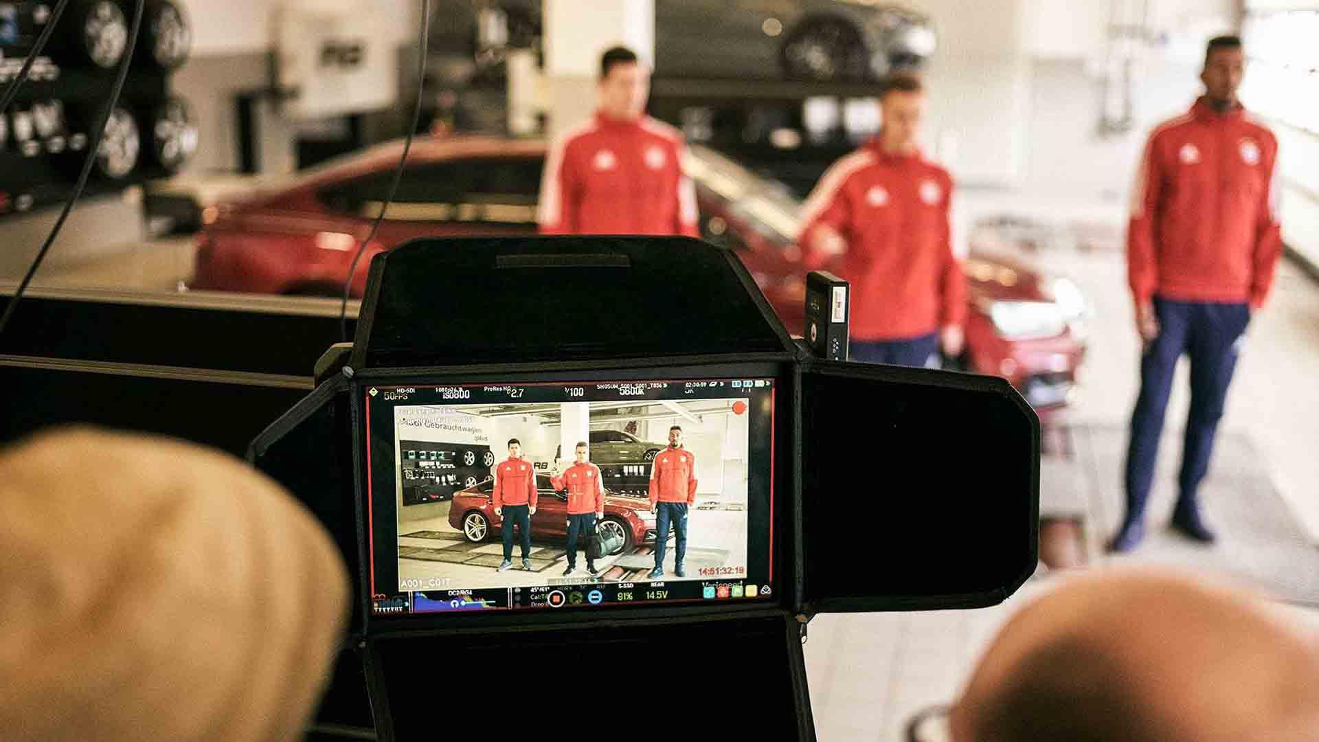 Das Bild zeigt im Hintergrund drei verschwommene Fussballer des FC Bayern Münchens. Vor ihnen steht eine Kamera mit einem Monitor. Die Schärfte des Bildes liegt auf diesem Monitor, sie sind darauf zu erkennen. Das Bild dient als Sliderbild für den Portfolioeintrag Audi / FC Bayern – Glückliche Nachbesitzer von Panda Pictures.