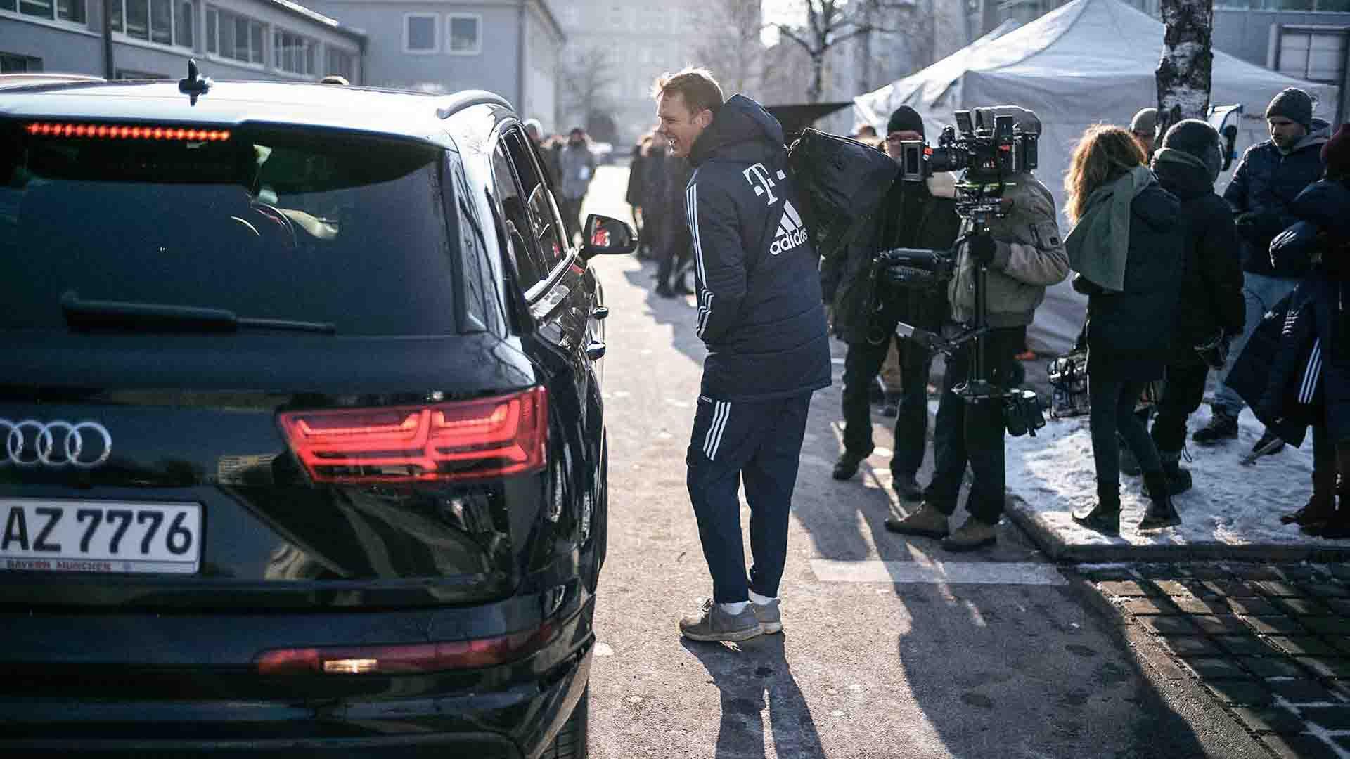Das Bild zeigt einen Mann. Er läuft neben einem Auto auf der rechten Seite entlang. Er hält eine Sporttasche in seiner Hand. Rechts neben ihm stehen Kameras und Kameramänner. Das Bild dient als Sliderbild für den Portfolioeintrag Audi / FC Bayern – Glückliche Nachbesitzer von Panda Pictures.