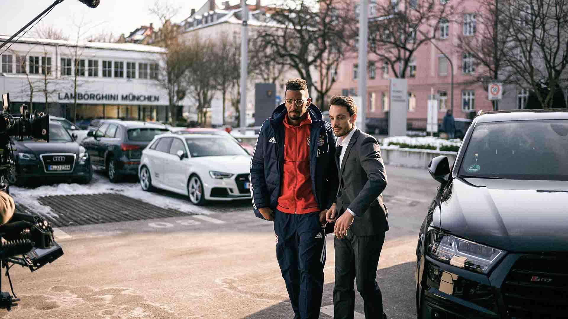 Das Bild zeigt den FC Bayern Fußballer Jérôme Boateng. Er wird von einem Mann in Anzug begleitet, ein Sercurtymann. Sie laufen neben einem parkenden Auto. Hinter ihnen stehen andere parkende Autos sowie Gebäude. Das Bild dient als Sliderbild für den Portfolioeintrag Audi / FC Bayern – Glückliche Nachbesitzer von Panda Pictures.