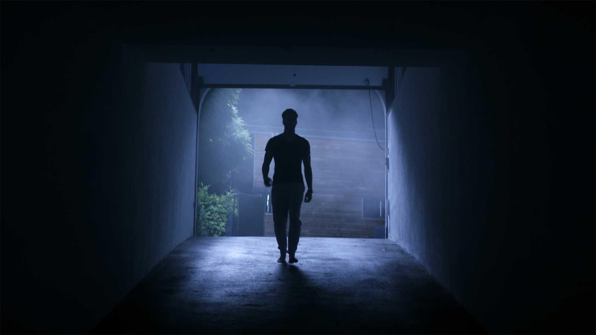 Das Bild zeigt eine Nachtkulisse. Ein Mann ist dabei in eine Garage zu laufen. Es ist so dunkel dass man nur seine Silhouette erkennt. Vor dem Eingang sieht man einen Lichtstrahl herunter fallen. Dahinter stehen Pflanzen. Das Bild dient als Sliderbild für den Portfolioeintrag BMW Connected Drive Home Alone von Panda Pictures.