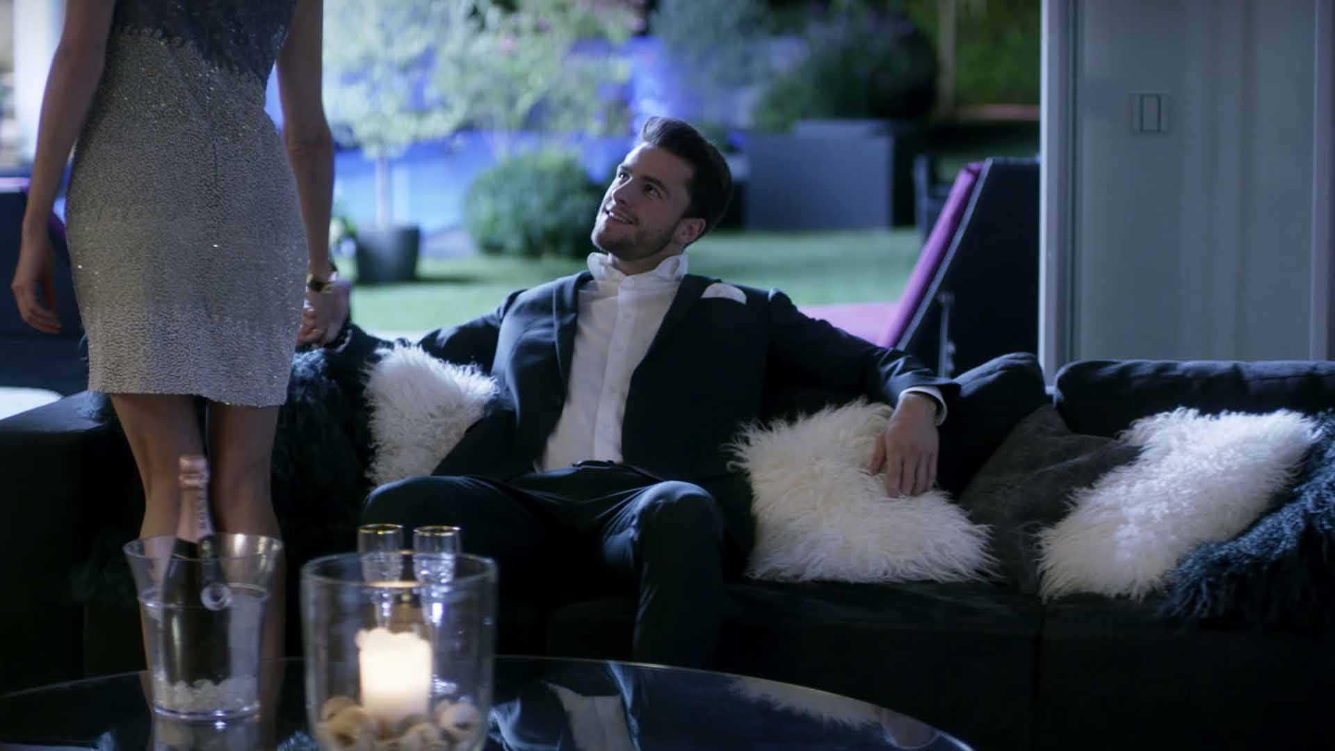 Das Bild zeigt einen Mann. Er sitzt auf einem Sofa. Unter ihm befindet sich ein Lammfell. Er trägt einen Anzug. Vor ihm steht ein Tisch mit einer Kerze. Eine Frau nimmt ihn an der Hand. Hinter ihm sieht man einen Garten. Das Bild dient als Sliderbild für den Portfolioeintrag BMW Connected Drive Home Alone von Panda Pictures.