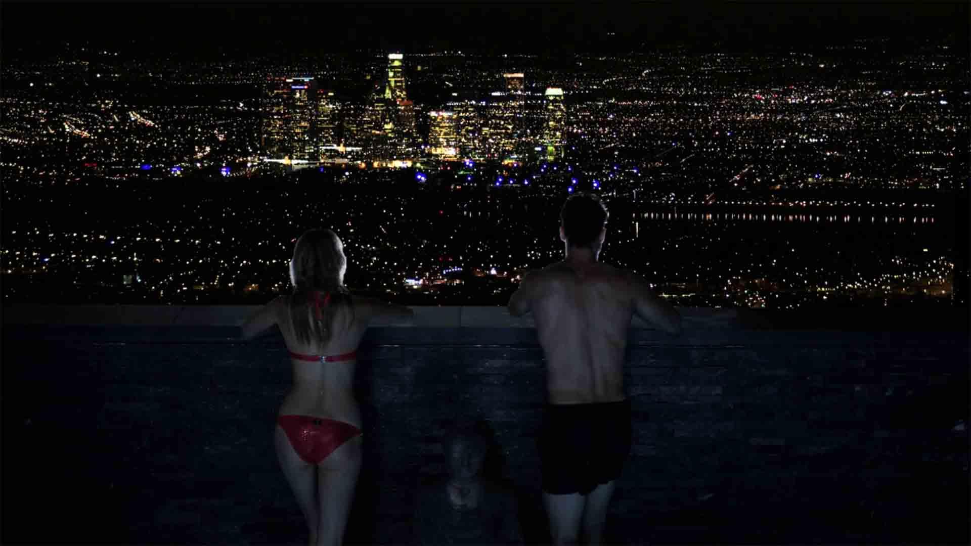 Das Bild zeigt die Skyline eine Stadt. Vor ihr stehen ein Mann und eine Frau in Badekleidung auf einem Balkon. Sie schauen sich die Skyline an. Es ist Nacht. Sie tragen Badekleidung. Der Mann trägt eine schwarze Badehose, die Frau trägt einen roten Bikini. Das Bild dient als Sliderbild für den Portfolioeintrag BMW Connected Drive Home Alone von Panda Pictures.