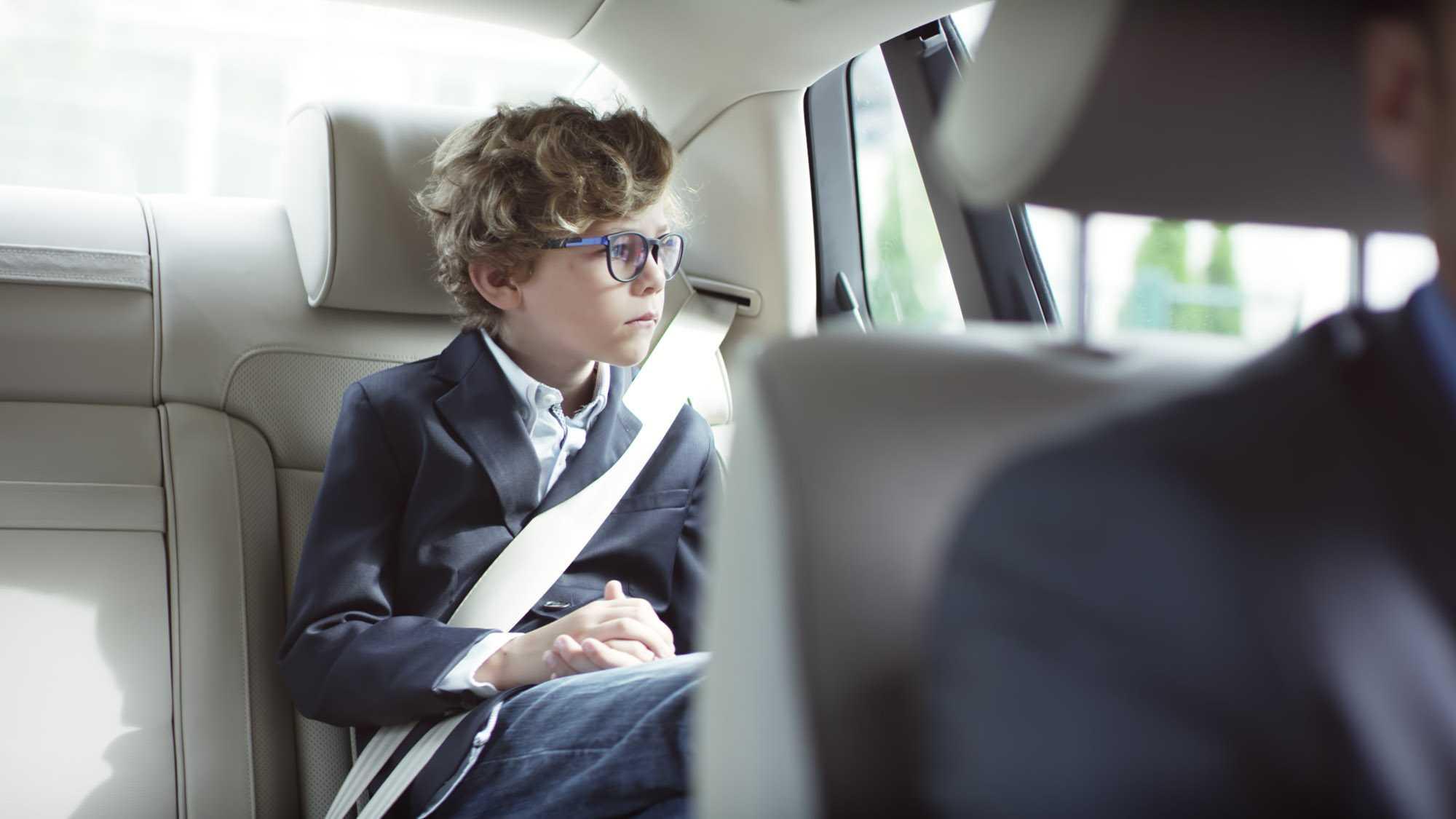 Das Bild zeigt einen Jungen. Dieser sitzt auf der Rückbank eines Autos. Er schaut gedankenverloren aus dem Fenster. Seine Hände liegen in seine Schoß. Er hat lockige Haare und eine schwarze Brille. Das Bild dient als Sliderbild für den Portfolioeintrag BMW Connected Drive Rivalitätskampf von Panda Pictures.