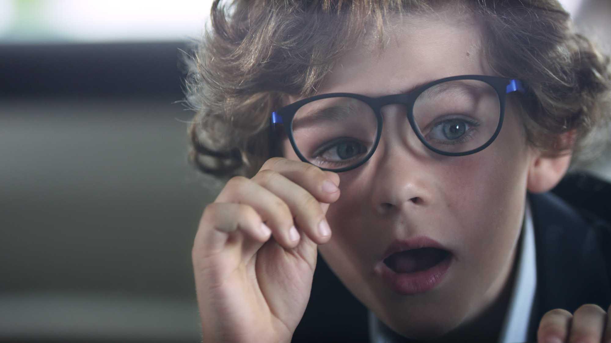 Das Bild zeigt einen Jungen. Er hat lockige Haare und trägt eine schwarze Brille. Er schiebt die Brille mit seiner Hand hoch. Das Bild dient als Sliderbild für den Portfolioeintrag BMW Connected Drive Rivalitätskampf von Panda Pictures.