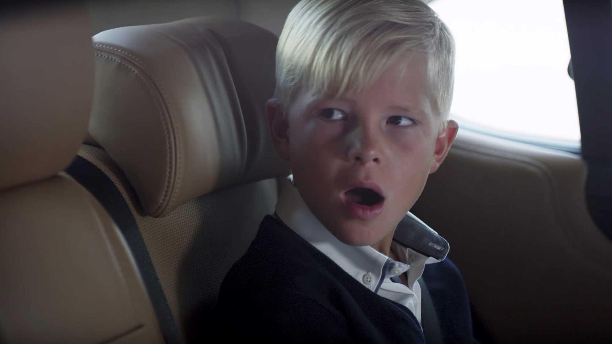 Das Bild zeigt einen Jungen. Er sitzt auf der Rückbank eines Autos. Er hat blonde Haare. Sein Mund ist geöffnet, er schaut verwundert. Die Sitze des Autos sind aus braunem Leder. Das Bild dient als Sliderbild für den Portfolioeintrag BMW Connected Drive Rivalitätskampf von Panda Pictures.