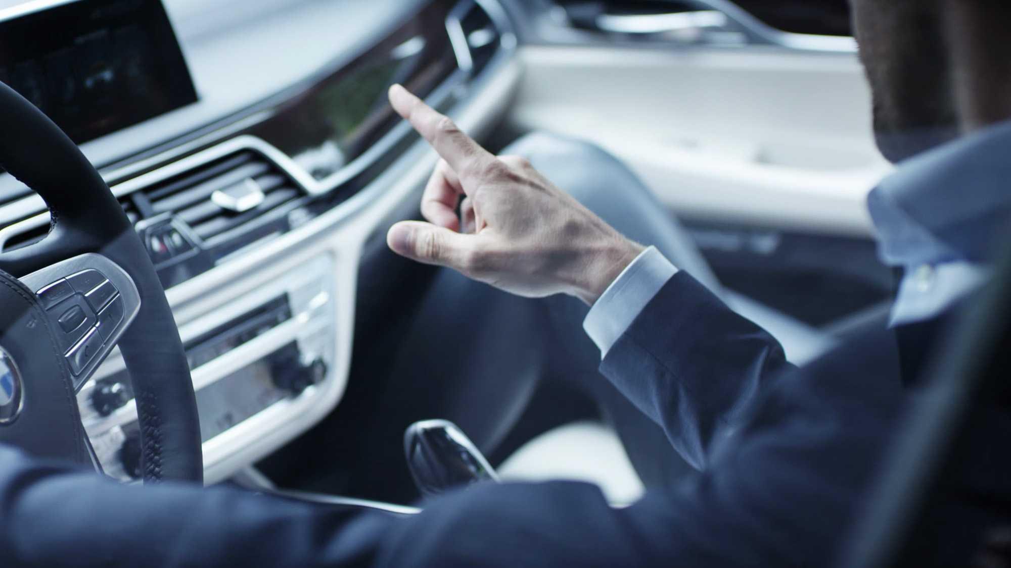 Das Bild zeigt eine Hand. Diese zeigt auf eine Mittelkonsole in einem Fahrzeug. Das Bild dient als Sliderbild für den Portfolioeintrag BMW Connected Drive Schweigefuchs von Panda Pictures.