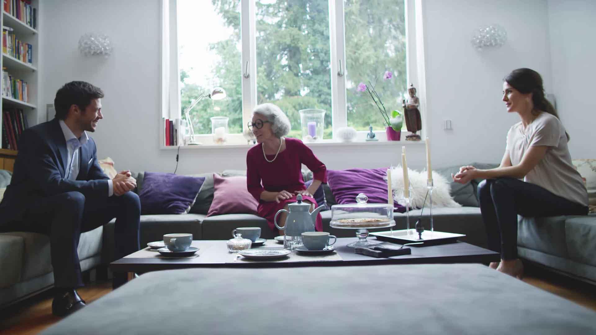 Das Bild zeigt einen Wohnraum. In diesem steht mittig ein Tisch. Auf dem Tisch sind verschiedene Tassen, Teller und eine Kanne zu sehen. Vor dem Tisch sitzt eine Frau. Sie unterhält sich mit einem Mann, der links neben ihr sitzt. Er trägt einen dunklen Anzug. Die Frau trägt eine schwarze, runde Brille. Neben ihr, auf der rechten Seite, sitzt eine andere Frau. Das Bild dient als Sliderbild für den Portfolioeintrag BMW Connected Drive Schweigefuchs von Panda Pictures.