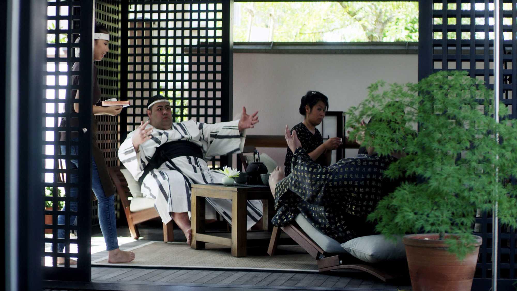 """Das Bild zeigt zwei Sumos, die auf Sesseln sitzen. Sie sitzen in einem Raum. Dieser ist durch japanische Trennwände abgestellt. Neben ihnen, auf der rechten Seite, sitzt eine Frau. Links von ihnen steht eine Frau. Sie hält etwas in der Hand. Es sieht aus, als würde sie die beiden bedienen. Das Bild dient als Sliderbild für den Portfolioeintrag """"BMW Connected Drive Sumos"""" von Panda Pictures."""