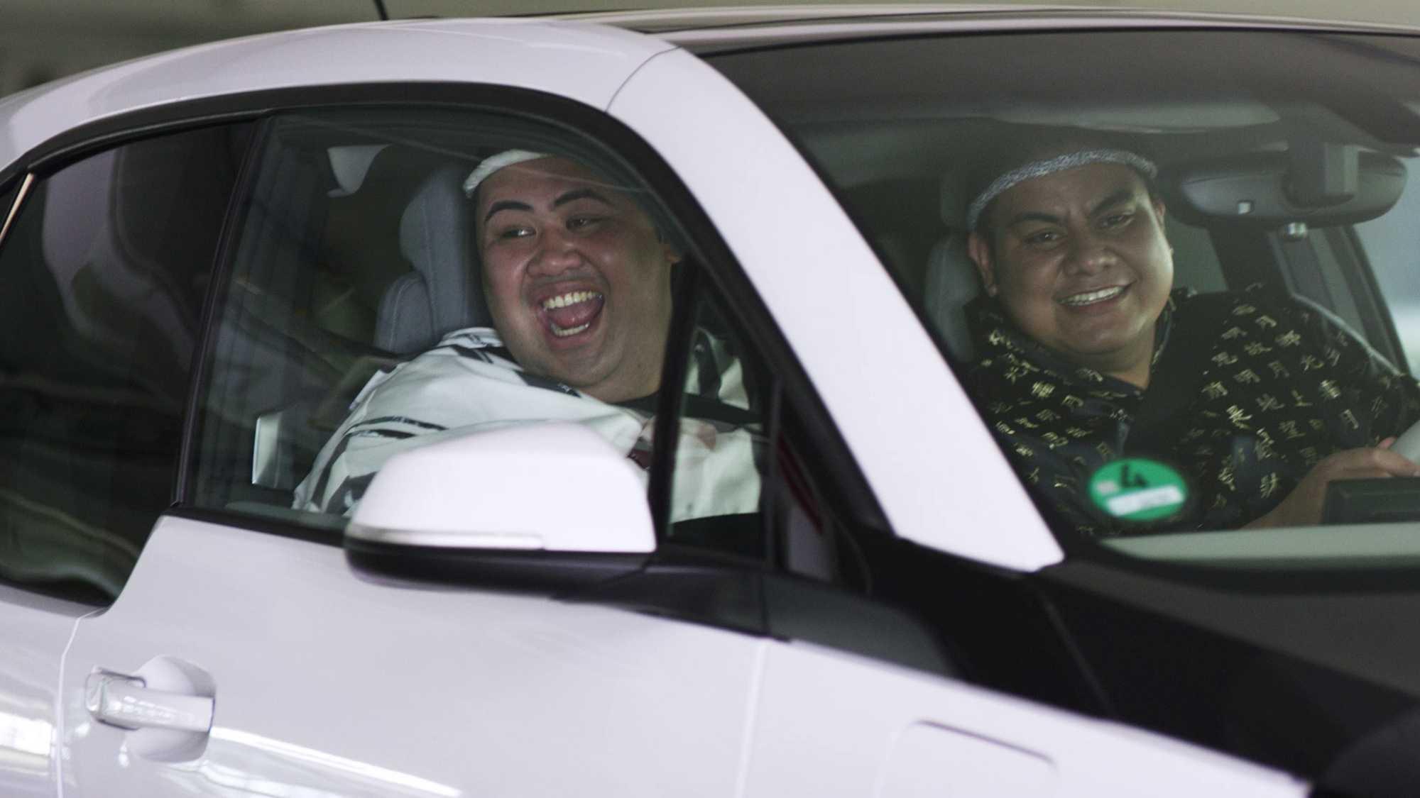 Das Bild zeigt ein Auto. In diesem sitzen zwei Sumos. Der Sumo, der auf der Beifahrerseite sitzt, schaut aus dem Fenster und lacht dabei. Das Bild dient als Sliderbild für den Portfolioeintrag BMW Connected Drive Sumos von Panda Pictures.