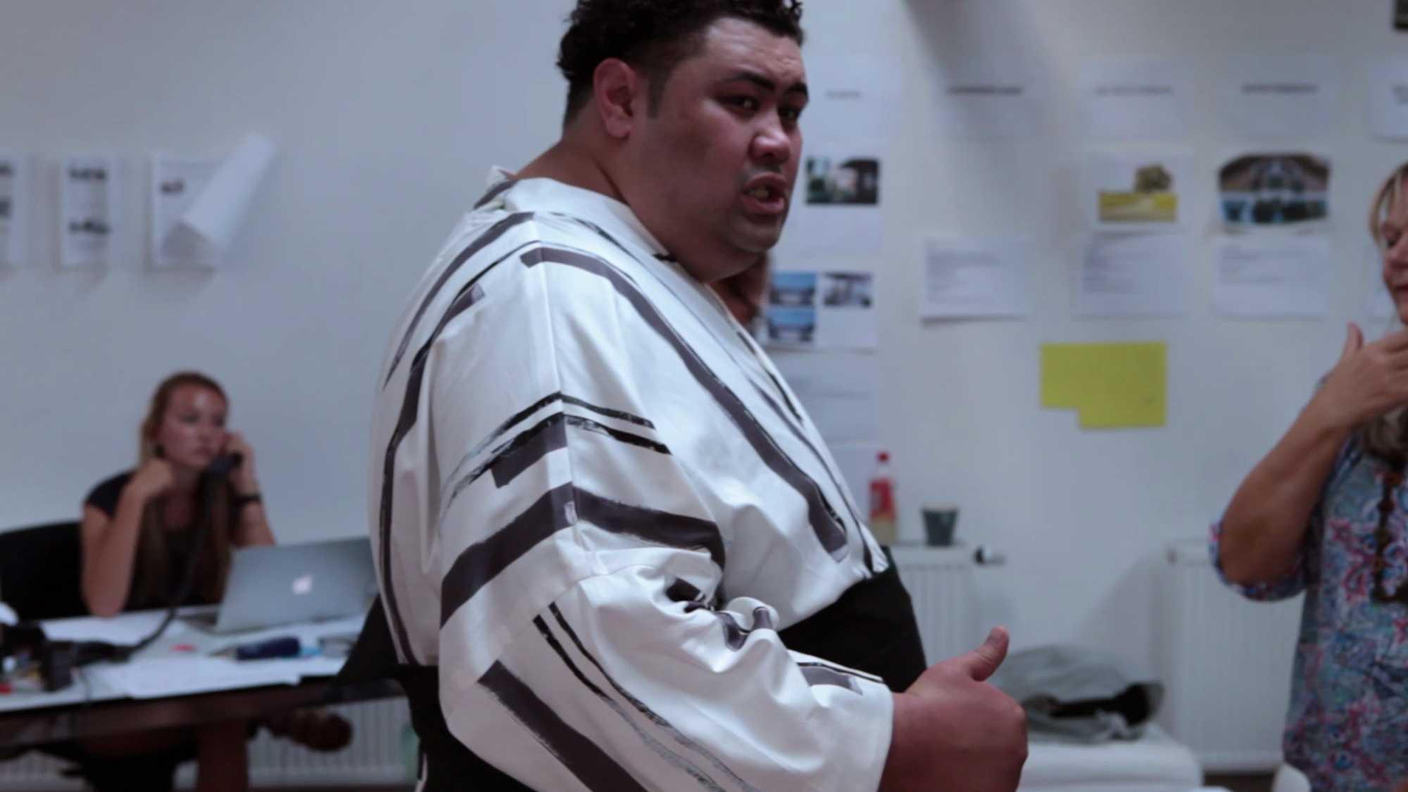 """Das Bild zeigt einen Mann. Er ist ein Sumo. Er steht in einem Raum. In diesem Raum sitzt eine Frau hinter ihm am Schreibtisch. An der Wand hängen Zettel. Neben ihm steht jemand, jedoch unkenntlich. Das Bild dient als Sliderbild für den Portfolioeintrag """"BMW Connected Drive Sumos"""" von Panda Pictures."""