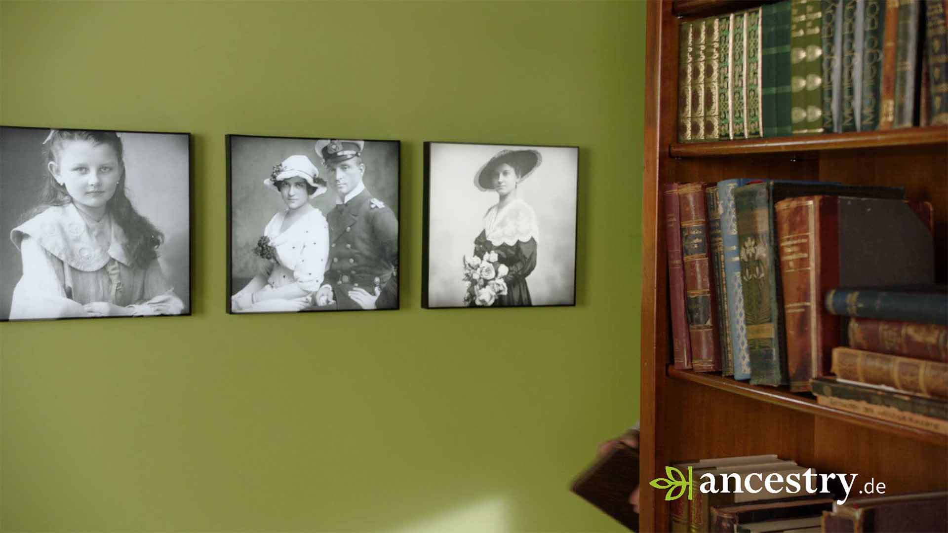 Das Bild zeigt ein Bücherregal. In diesem stehen ältere Bücher. Links neben dem Bücherregal ist eine grüne Wand zu sehen. An dieser Wand sind drei Bilder angebracht. Auf diesen Bildern ist eine Frau, ein Paar und ein Mädchen zu sehen. Das Bild dient als Sliderbild für den Portfolioeintrag Ancestry – DRTV Spot von Panda Pictures.
