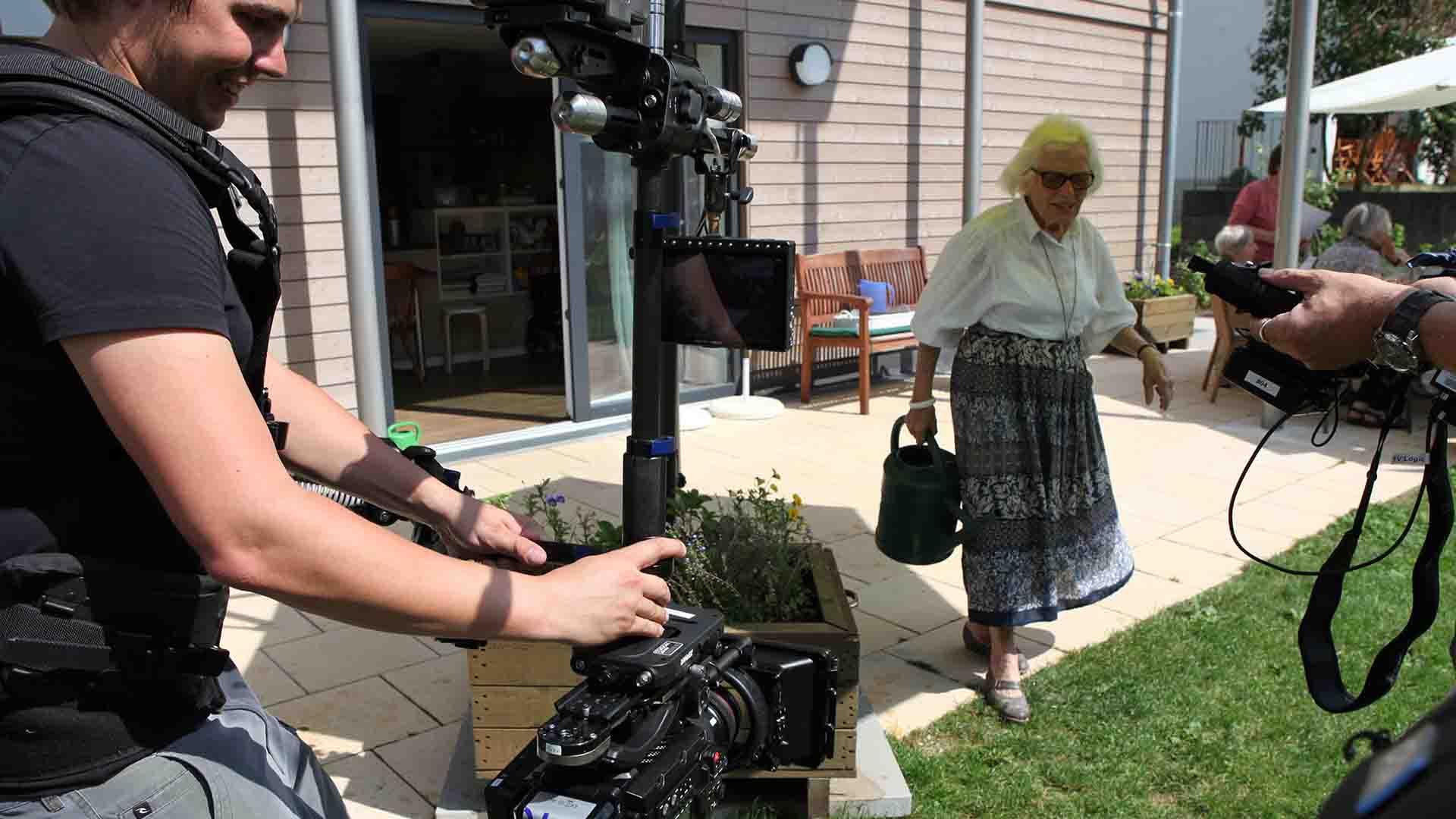 """Das Bild zeigt auf der linken Seite einen Mann, der eine Kamera führt. Er filmt eine ältere Dame, die von einer Terrasse auf eine Wiese läuft. In ihrer Hand hält sie eine Tasche. Sie trägt eine Brille. Das Bild dient als Sliderbild für den Portfolioeintrag """"MARO Demenz WG Weilheim"""" von Panda Pictures."""