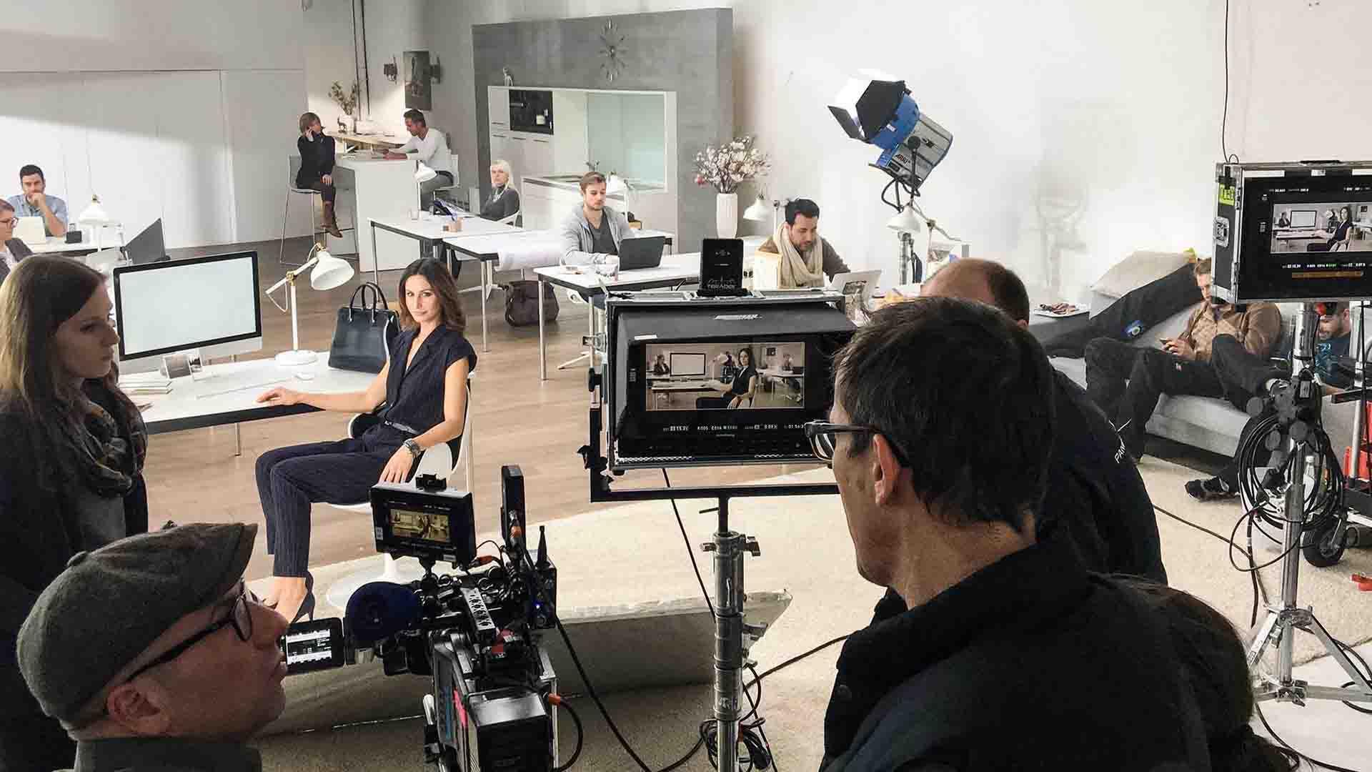 Das Bild zeigt ein Büro. In diesem Büro stehen viele Schreibtische an denen Menschen arbeiten. Vor dem Büro steht eine Kamera mit Monitor. Auf dem Monitor sieht man das Büro. An einem Schreibtisch sitzt eine Frau die sich in Richtung der Kamera gedreht hat. Vor dem Monitor stehen Männer die sich unterhalten. Das Bild dient als Sliderbild für den Portfolioeintrag MADELEINE Mode – DRTV Spot von Panda Pictures.
