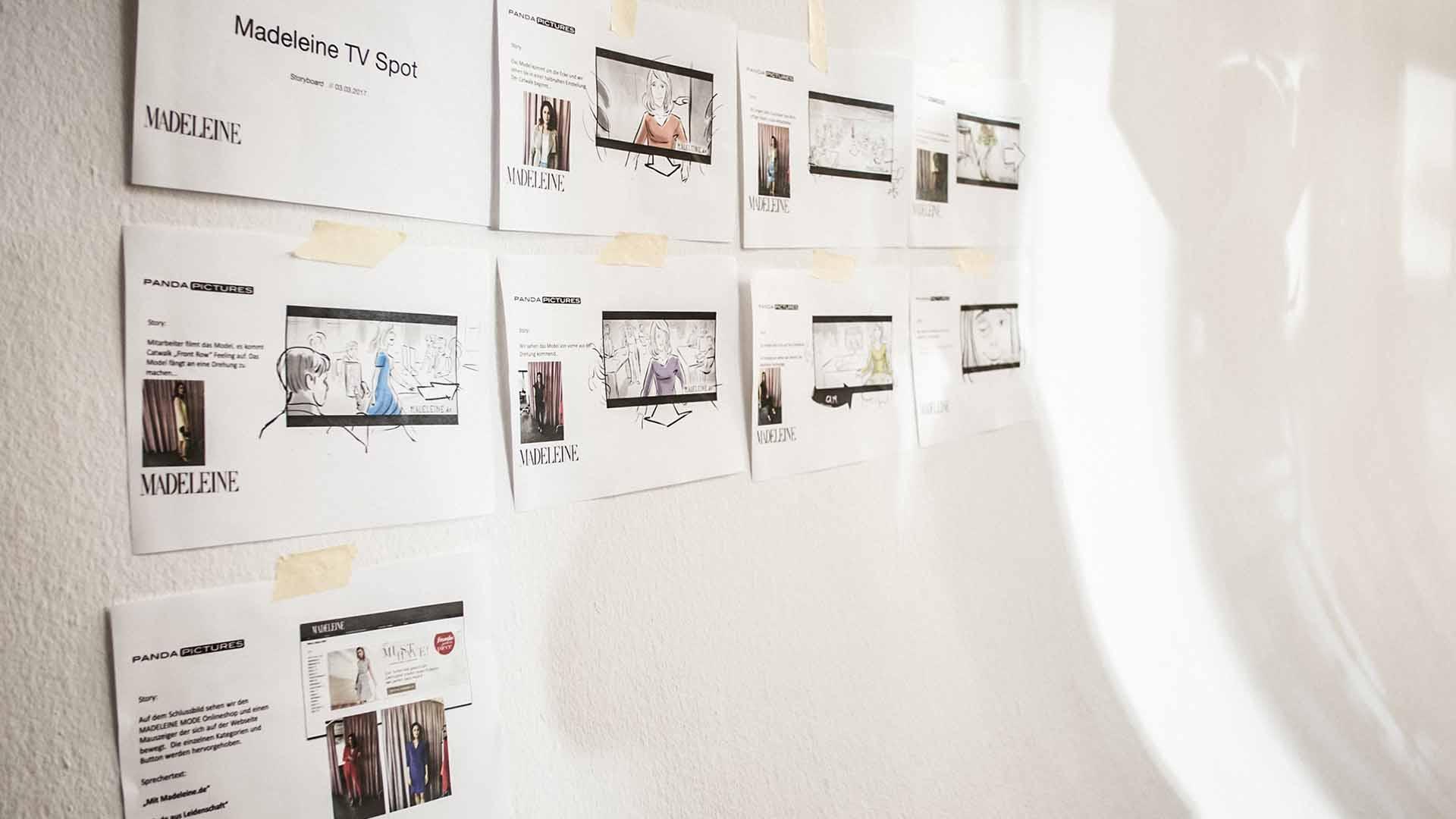 Das Bild zeigt eine Wand. An dieser Wand hängen Zettel. Diese Zettel zeigen verschiedene Szenen. Diese Szenen stammen von einem Werbespot. Sie sind gezeichnet. Das Bild dient als Sliderbild für den Portfolioeintrag MADELEINE Mode – DRTV Spot von Panda Pictures.