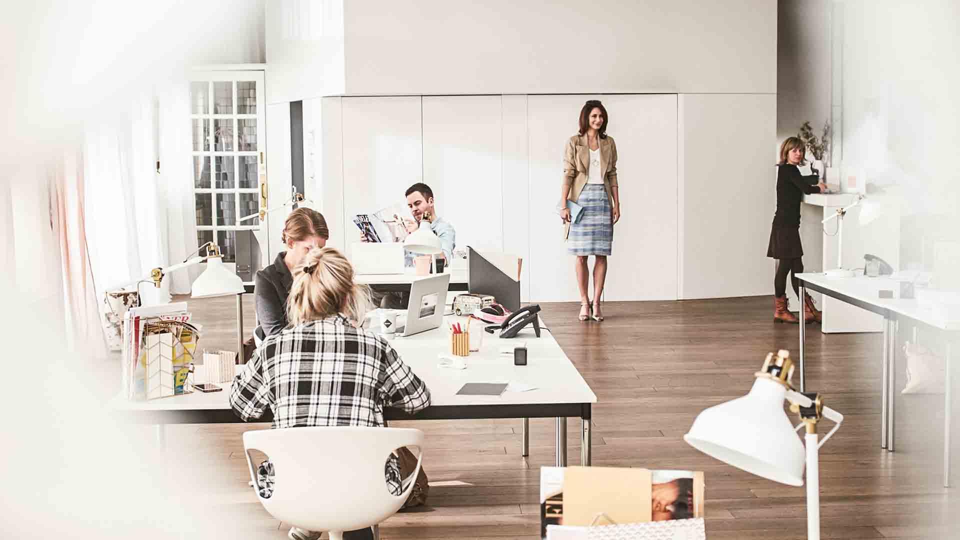 Das Bild zeigt eine Frau die sich am ende eines Raumes befindet. Sie ist kurz davor einen Lauf hinzulegen. Links von ihr sitzen Menschen an Schreibtischen und arbeiten. Das Bild dient als Sliderbild für den Portfolioeintrag MADELEINE Mode – DRTV Spot von Panda Pictures.