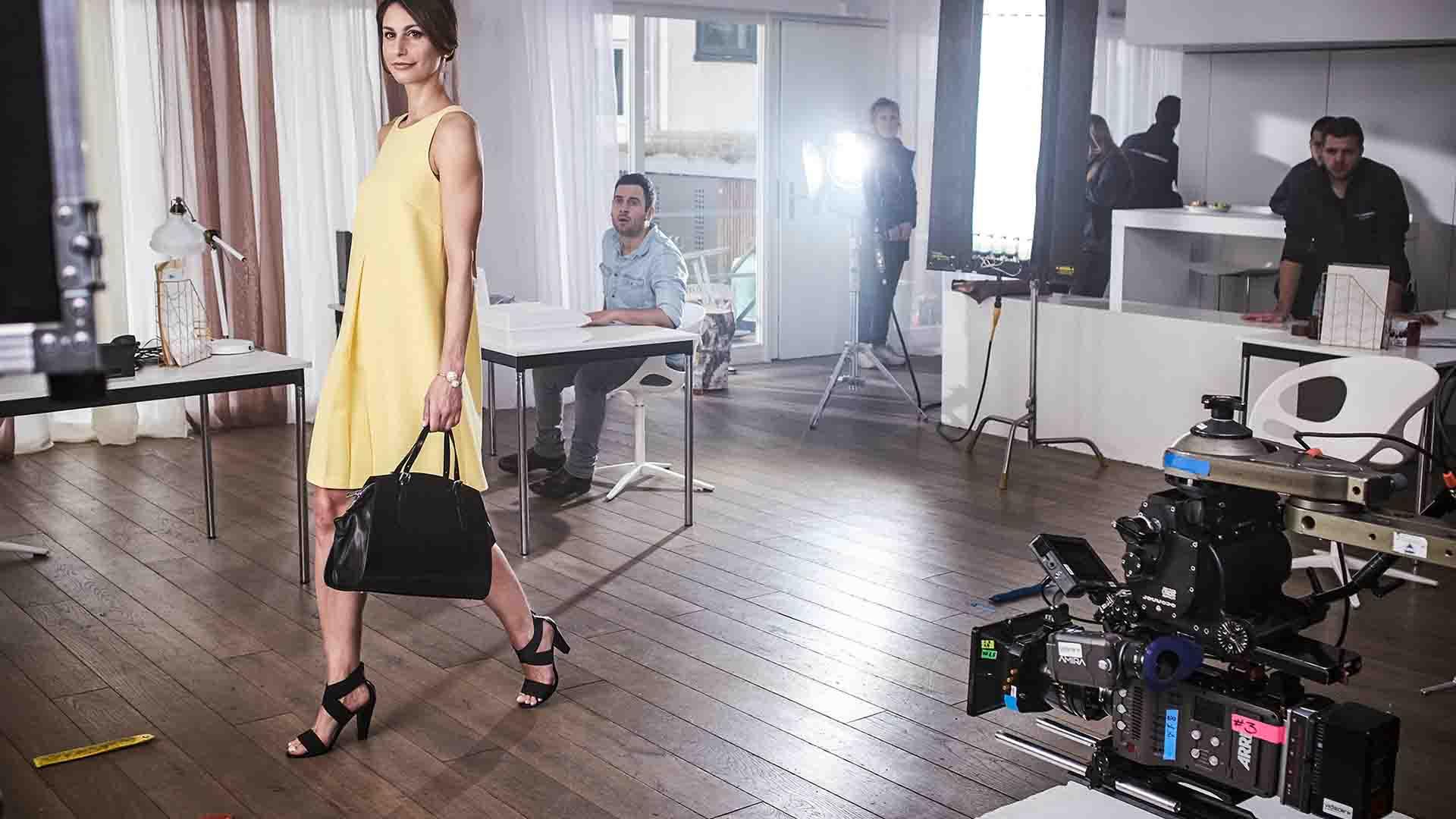Das Bild zeigt einen Raum. Durch diesen Raum läuft eine Frau mit einem gelben Kleid. Sie trägt eine schwarze Handtasche. Rechts von ihr ist eine Kamera angebracht die sie filmt. Hinter ihr steht ein Licht, dass sie anleuchtet sowie weitere Leute des Kamerateams. Das Bild dient als Sliderbild für den Portfolioeintrag MADELEINE Mode – DRTV Spot von Panda Pictures.