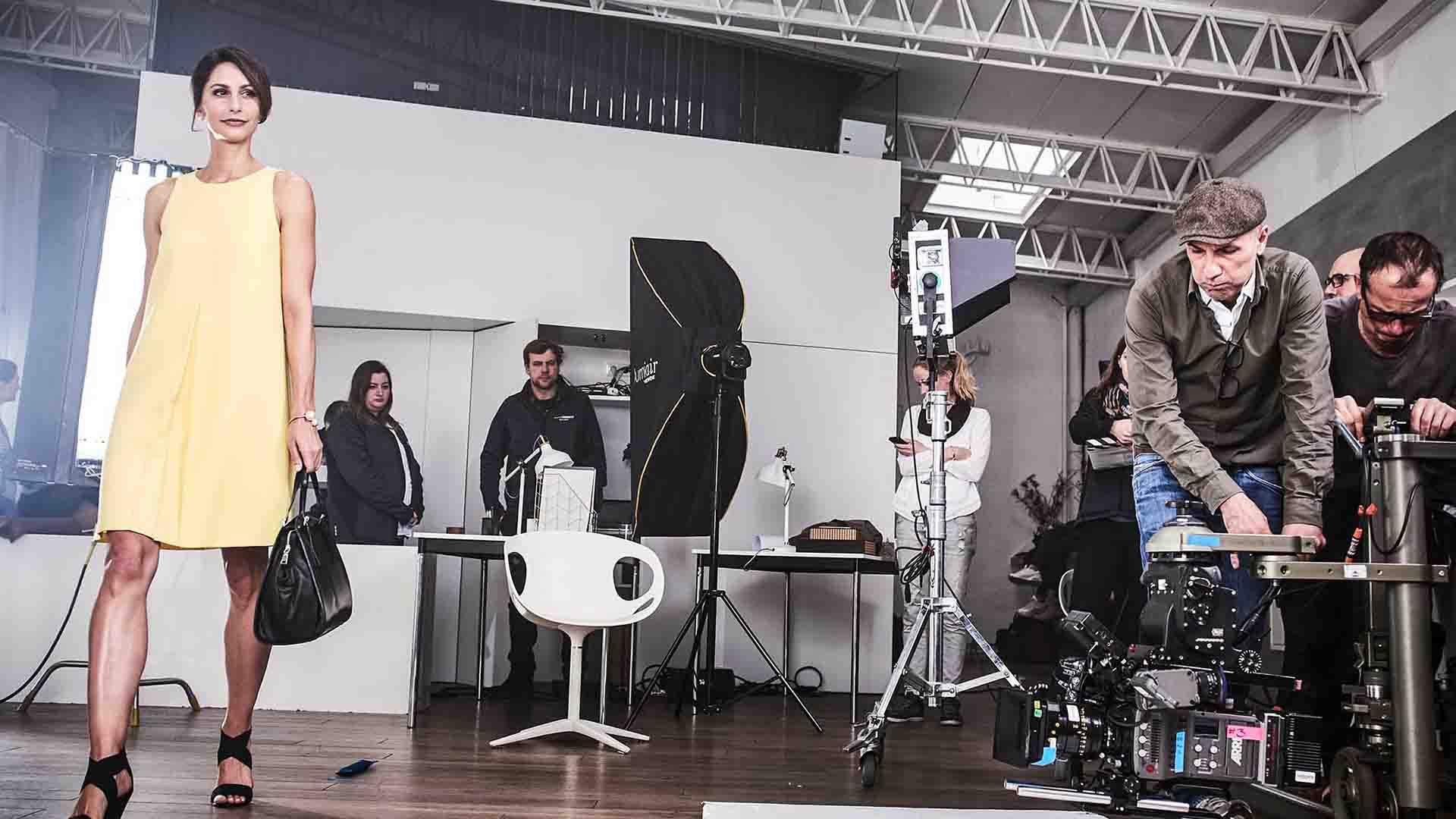 Das Bild zeigt eine Frau. Sie trägt ein gelbes Kleid und eine schwarze Handtasche. Neben ihr und hinter ihr sind viele Menschen. Diese gehören zu einem Kamerateam dass sie filmt. Das Bild dient als Sliderbild für den Portfolioeintrag MADELEINE Mode – DRTV Spot von Panda Pictures.