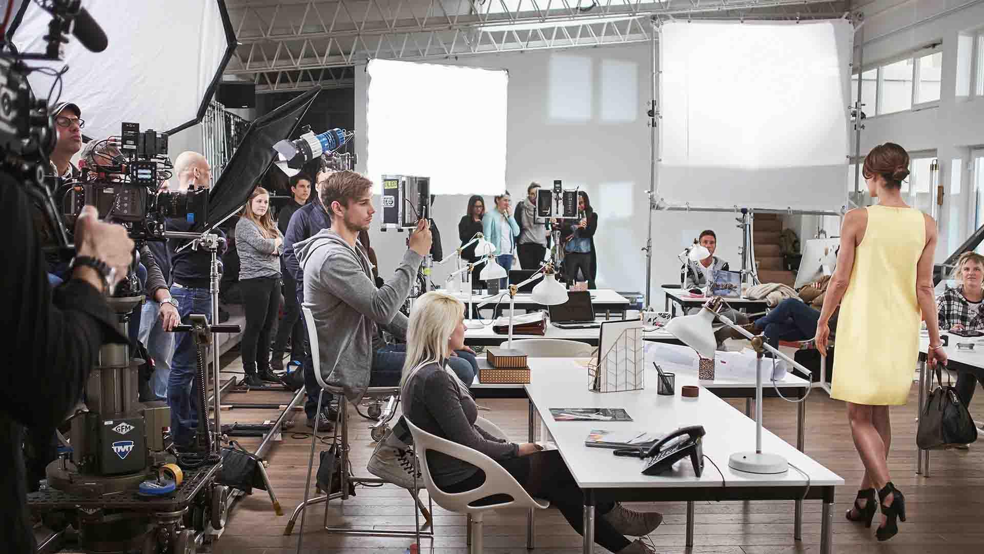 Das Bild zeigt eine Frau in einem gelben Kleid. Sie läuft über einen Laufsteg in einem Büro. An den Rändern des Büros stehen Menschen die die Frau beobachten. Ein Mann filmt sie mit seinem Handy. Kameras und Lichter sind aufgestellt, die die Frau filmen. Das Bild dient als Sliderbild für den Portfolioeintrag MADELEINE Mode – DRTV Spot von Panda Pictures.