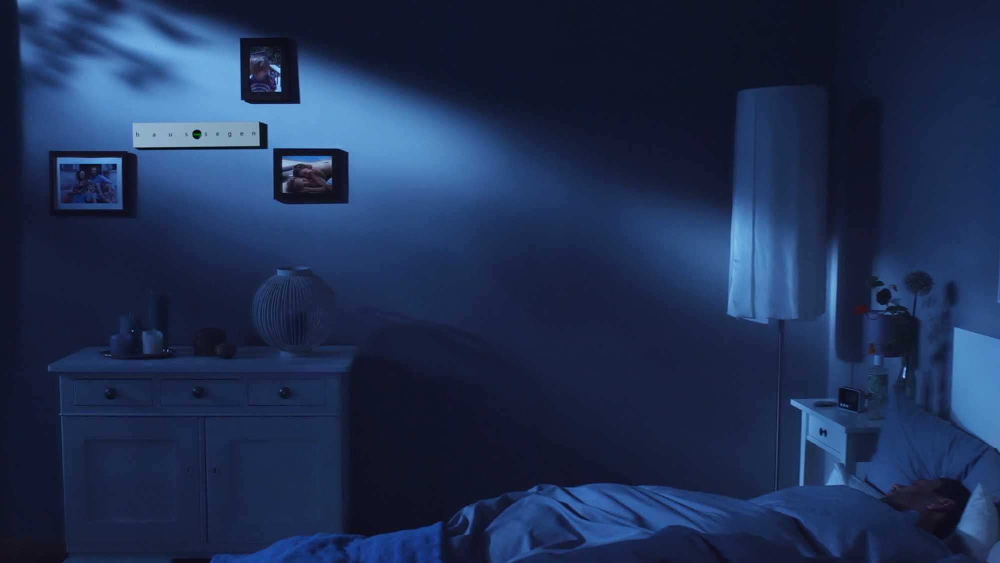 Das Bild zeigt eine blaue Wand in einem Raum. In diesem Raum steht ein Bett und eine Kommode. Es ist Nacht. Die Wand ist blau gefärbt. An ihr hängen Bilder. Dazwischen ist eine Wasserwaage aufgehängt. Diese ist gerade an der Wand zu sehen. Das Bild dient als Sliderbild für den Portfolioeintrag Ohropax Haussegen von Panda Pictures.