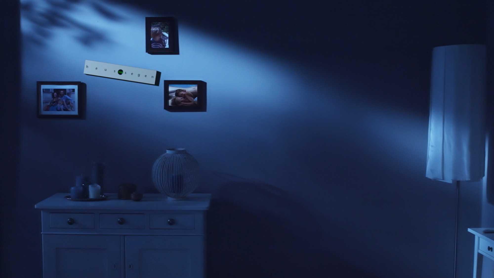 Das Bild zeigt eine blaue Wand in einem Raum. In diesem Raum steht ein Bett und eine Kommode. Es ist Nacht. Die Wand ist blau gefärbt. An ihr hängen Bilder. Dazwischen ist eine Wasserwaage aufgehängt. Diese hängt schief. Das Bild dient als Sliderbild für den Portfolioeintrag Ohropax Haussegen von Panda Pictures.