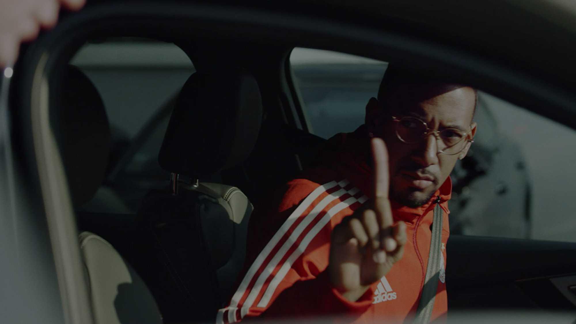 Das Bild zeigt Jérôme Boateng der sich in einem Auto befindet. Er hebt seinen Zeigefinger in die Höhe. Das Bild dient als verdunkeltes Titelbild für den Portfolioeintrag Audi / FC Bayern – Glückliche Nachbesitzer von Panda Pictures.
