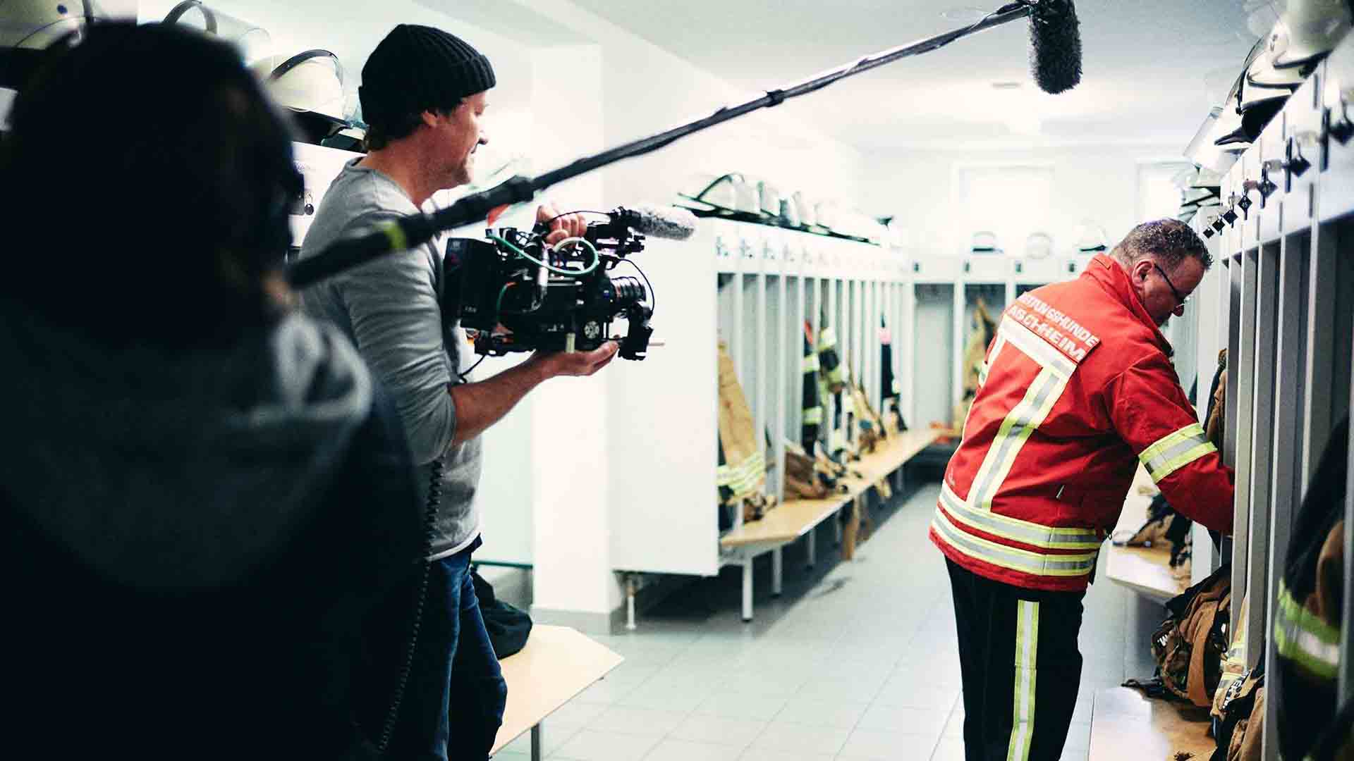 Das Bild zeigt einen Feuerwehrmann der in einer Umkleidekabine steht. Er trägt seine Uniform und holt etwas aus einem Spind. Neben ihm steht ein Kameramann der ihn filmt. Neben dem Kameramann steht ein Tonassistent der ein Tongerät hält. Das Bild dient als Sliderbild für den Portfolioeintrag Audi | FC Bayern München Ehrenrunde von Panda Pictures.