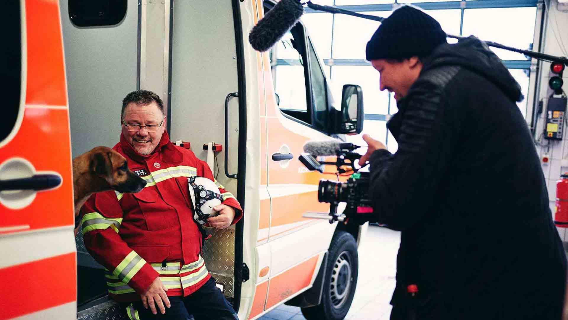 Das Bild zeigt einen Krankenwangen. Die Schiebetüren des Krankenwagens sind geöffnet. In dem Eingang sitzt ein Feuerwehrmann mit einem Hund. Er trägt seine Uniform und hält seinen Helm in der Hand. Vor ihm steht ein Kameramann der eine Kamera auf ihn richtet. Er wird gefilmt. Über dem Kameramann schwebt ein Tongerät. Das Bild dient als Sliderbild für den Portfolioeintrag Audi | FC Bayern München Ehrenrunde von Panda Pictures.