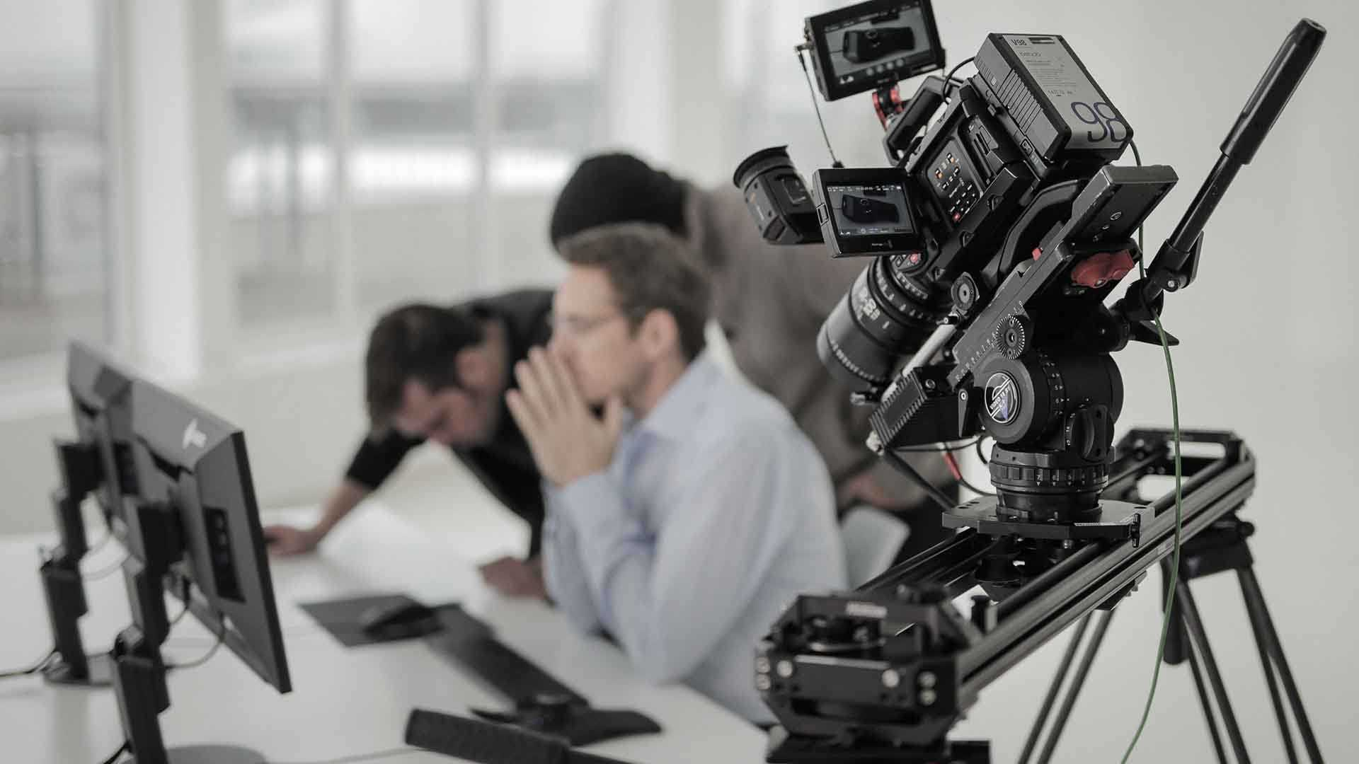 Das Bild zeigt eine Kamera. Diese Kamera ist so positioniert, dass sie einen Mann filmt. Dieser Mann sitzt an einem Schreibtisch. Auf diesem Schreibtisch steht ein Computer mit Equipment. Um den Mann herum stehen nochmals zwei Männer. Der Fokus des Bildes liegt auf der Kamera, diese ist scharf gestellt, der Rest des Bildes ist unscharf. Das Bild dient als Sliderbild für den Portfolioeintrag 3Dconnexion SpaceMouse von Panda Pictures.